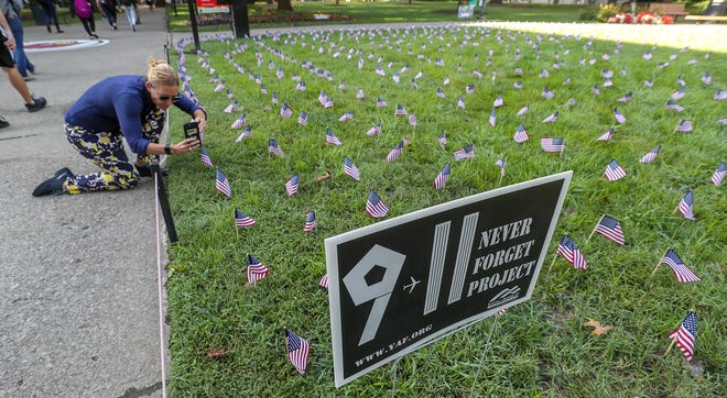 Alicia Kelso, with the UofL's Office of Communications takes a photo of nearly 3000 flags that were placed in the quad area at the University of Louisville by students remembering the attacks of September 11, 2001.  The flags represent the victims killed in the terrorist attacks 17 years ago.September 11, 2018
