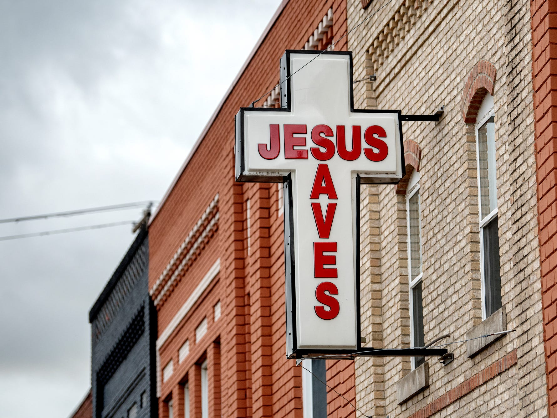 The 'Jesus Saves' sign above the City Rescue Mission photographed on Monday, Sept. 10, 2018, in downtown Lansing. The mission is located across Michigan Avenue from the site where the Gillespie Group is planning to build a grocery store and hotel.