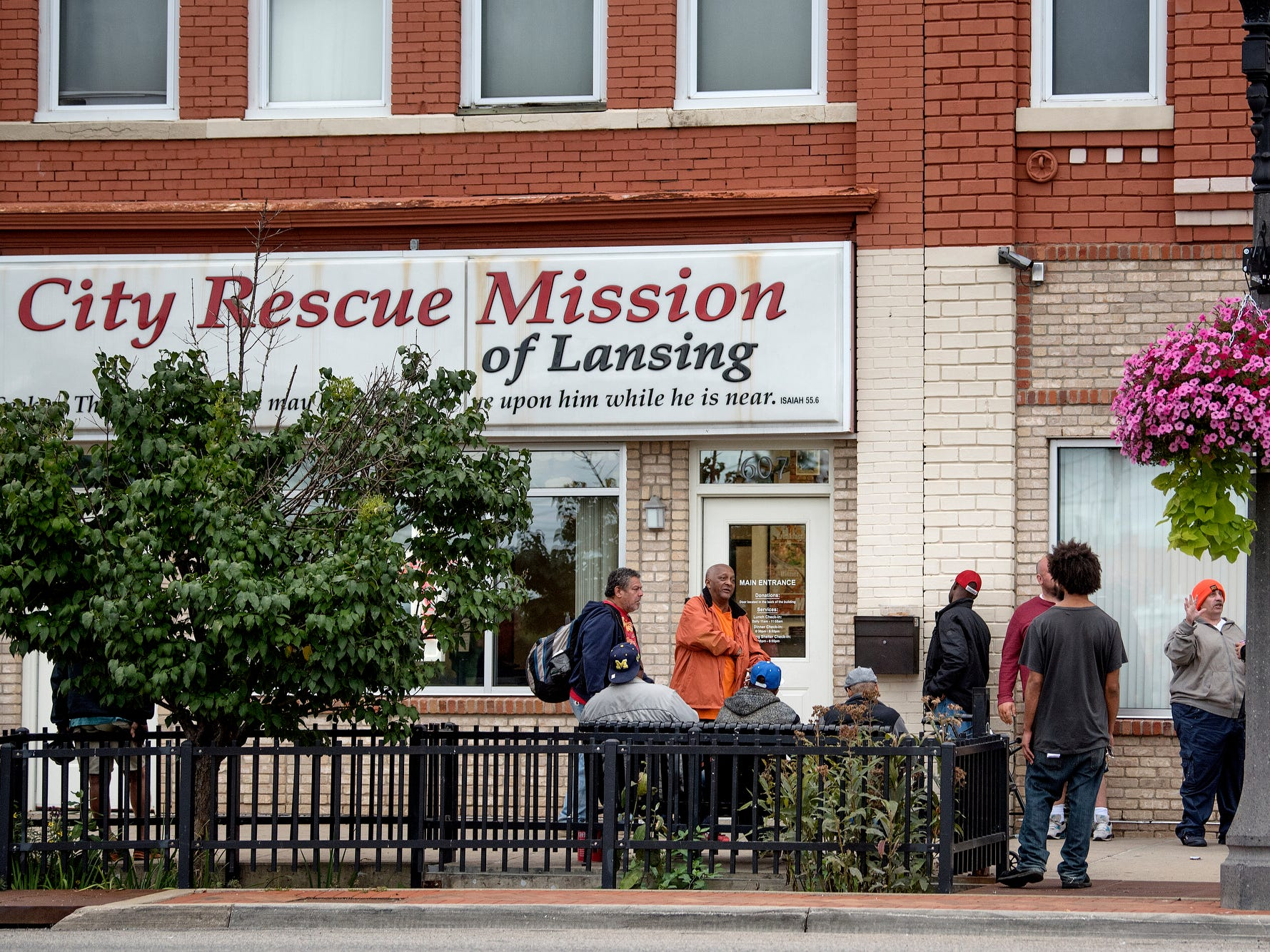 A line forms outside the City Rescue Mission before dinnertime on Monday, Sept. 10, 2018, in downtown Lansing. The mission is located across Michigan Avenue from the site where the Gillespie Group is planning to build a grocery store and hotel.