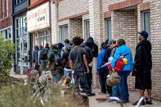 Lines form often outside the City Rescue Mission of Lansing building on East Michigan Avenue before it opens for dinnertime. The building helps men who may identify as homeless or at-risk.