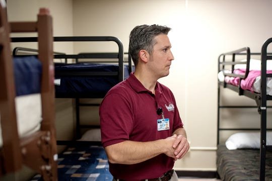 Executive Director Mark Criss talks about the facility in the sleeping quarters during a tour of the City Rescue Mission on Tuesday, Sept. 4, 2018, in downtown Lansing.