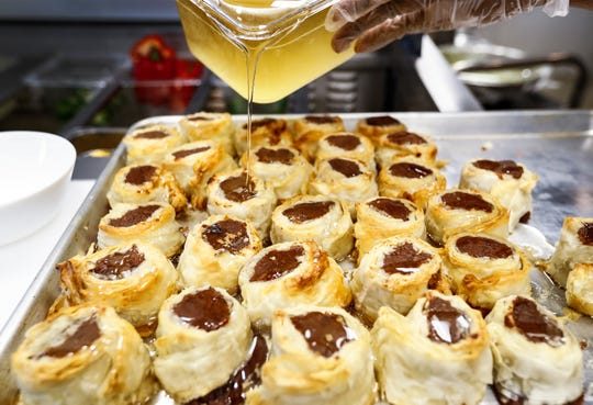 Global Cafe Sudanese chef Ibtisam Salih pours simple syrup over chocolate Basta pastry desserts in the 2,500-square-foot restaurant inside Crosstown Concourse. The cafe features dishes from Nepalese, Syrian and Sudanese immigrants or refugees.