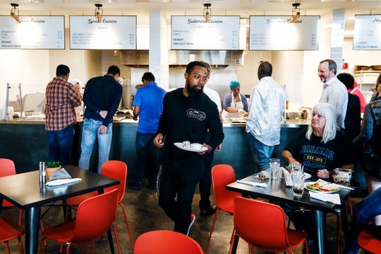 Global Cafe costumers order featured dishes from Venezuela, Syria and Sudan made by immigrants or refugees inside Crosstown Concourse.