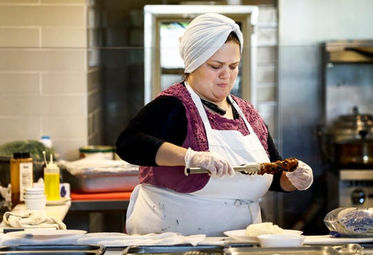 Global Cafe Syrian chef Fayha Sakkan prepares a chicken kobab in the 2,500-square-foot restaurant inside Crosstown Concourse.
