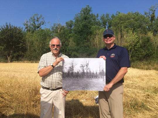 Maj. Brian Faltinson, a Wisconsin Army National Guard historian, (right) stands with the mayor of Sergy, France, at the site of what was a temporary cemetery for 32nd Red Arrow Division soldiers from Wisconsin and Michigan killed during the Second Battle of the Marne in July 1918.