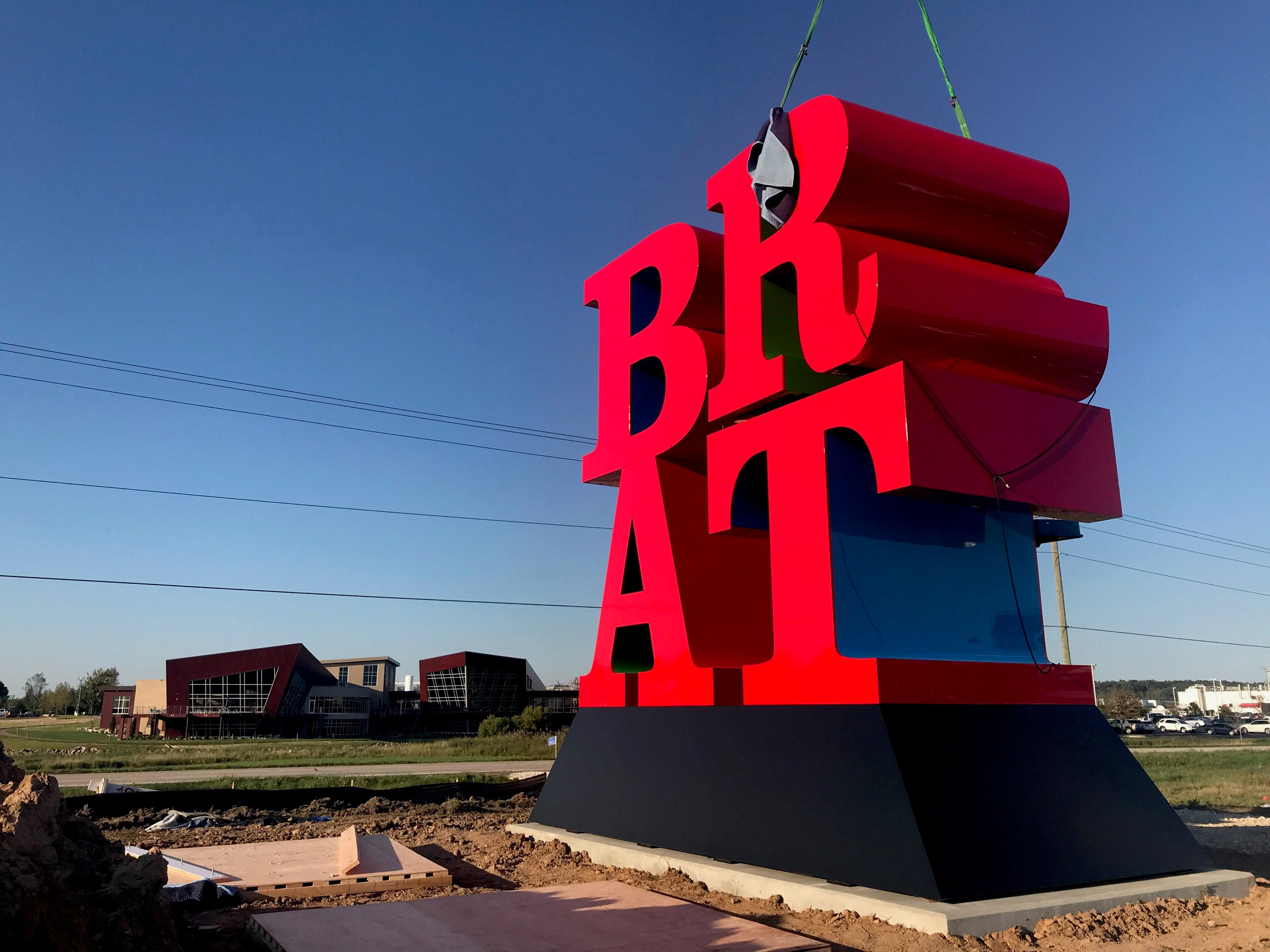The letter R is lowered into place.  Johnsonville installed what's said to be one of Robert Indiana's last pieces of art -- a sculpture spelling out the word BRAT -- at its headquarters in Sheboygan Falls on Tuesday, September 11, 2018. The tribute to bratwurst was commissioned by the owners of Johnsonville Sausage.