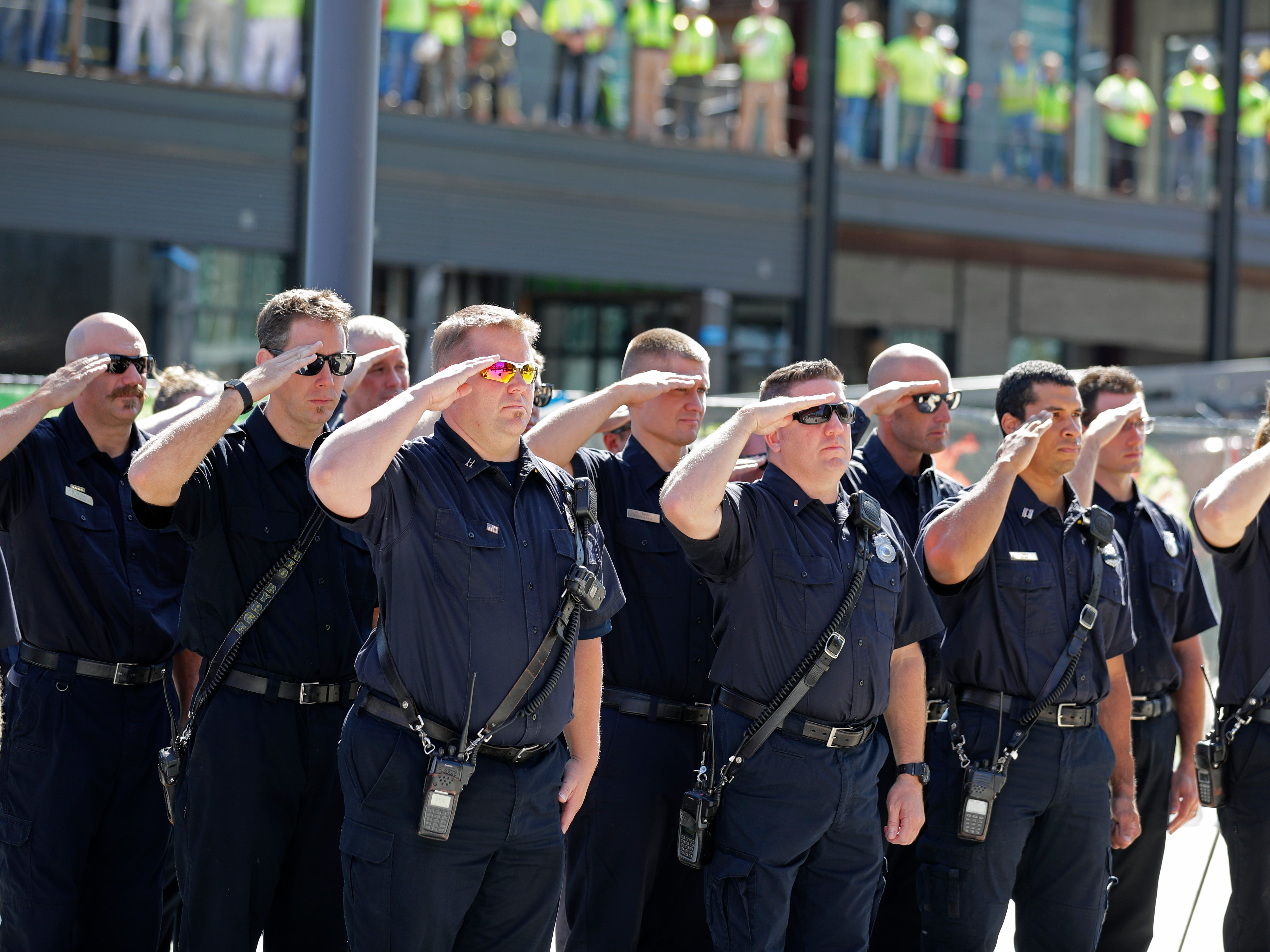 Firefighters salute as the names of firefighters who lost their lives responding to the Sept. 11, 2001, attacks on the World Trade Center in New York are read.