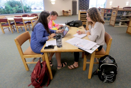 Madison Vogel (front left), a University of Wisconsin-Sheboygan freshman from Kiel whose major is undecided; Emma Egbert (right), a senior at Sheboygan Lutheran High School taking a college class; and Justin Landgraf, a University of Wisconsin Sheboygan junior majoring in elementary education, work on a project for their introduction to psychology class at the campus library. UW-Sheboygan County is now under the UW-Green Bay umbrella.