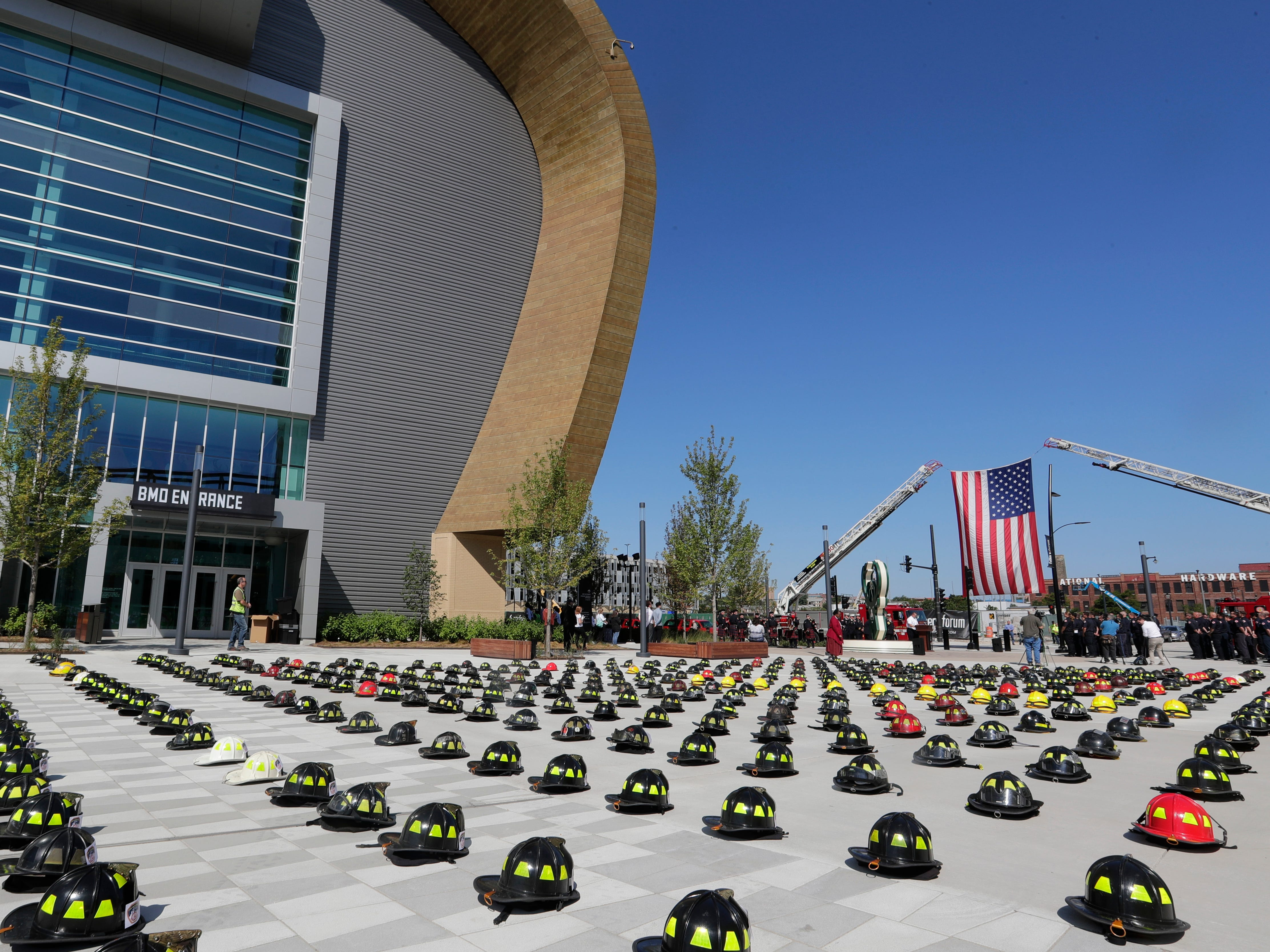 The Milwaukee Fire Department pays tribute to the losses suffered during the terror attacks on Sept. 11, 2001, during a ceremony Tuesday at Fiserv Forum commemorating the 17th anniversary of the attacks. Two fire department ladder trucks display the American flag and 343 helmets representing firefighters who perished in the attacks are also displayed. Uniformed personnel read the names  of those firefighters who perished.