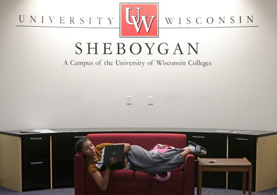 A University of Wisconsin-Green Bay, Sheboygan Campus student relaxes on a couch and works on her laptop while waiting for a class. The Sheboygan campus will see one of the highest rises in student fees next year: $124 over two semesters.