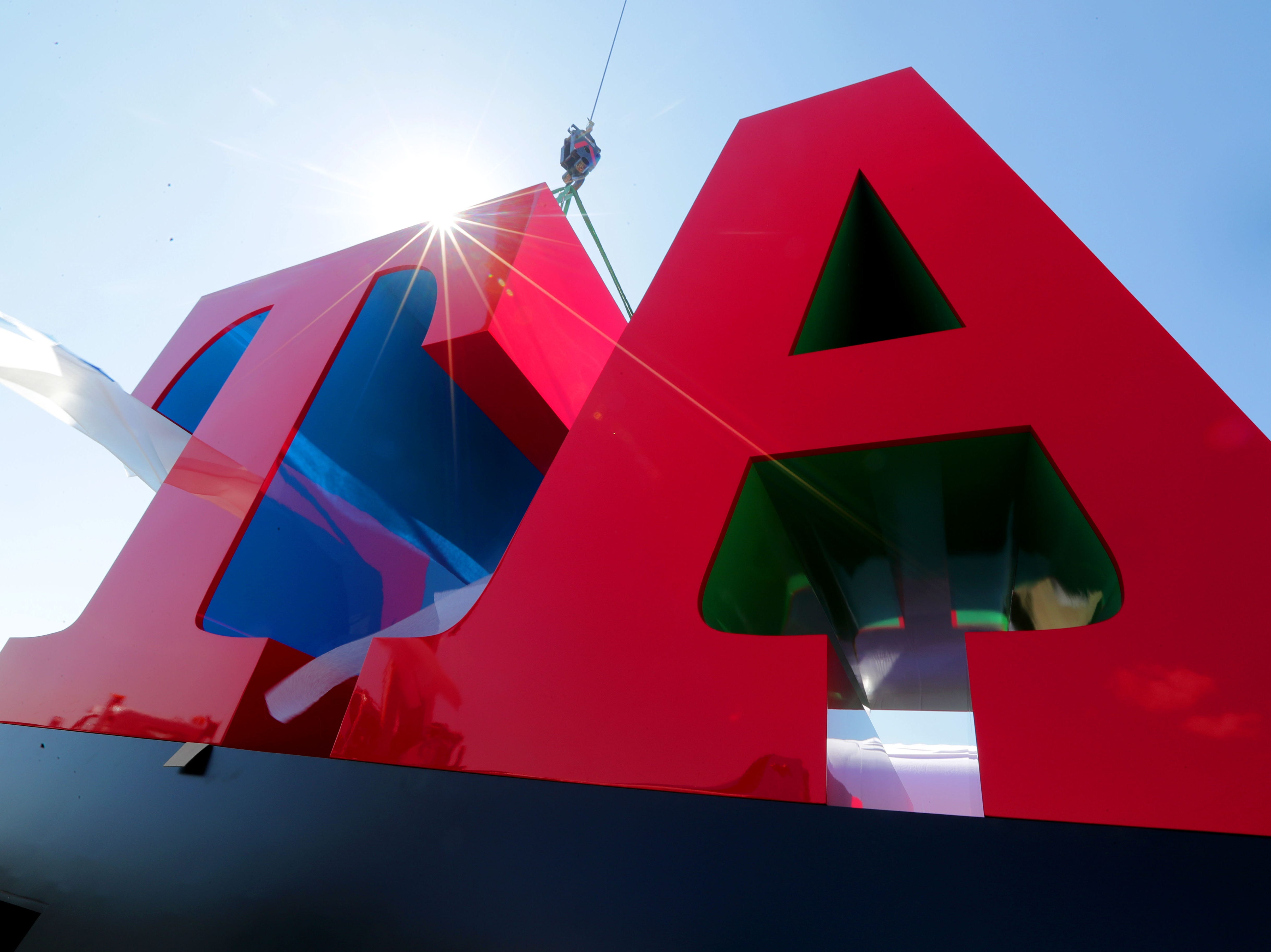 The letters T and A are placed onto a pedestal. The B and R will be placed on top. Johnsonville Sausage installed one of Robert Indiana's last pieces of art – a sculpture spelling out the word BRAT at its headquarters in Sheboygan Falls on Tuesday.