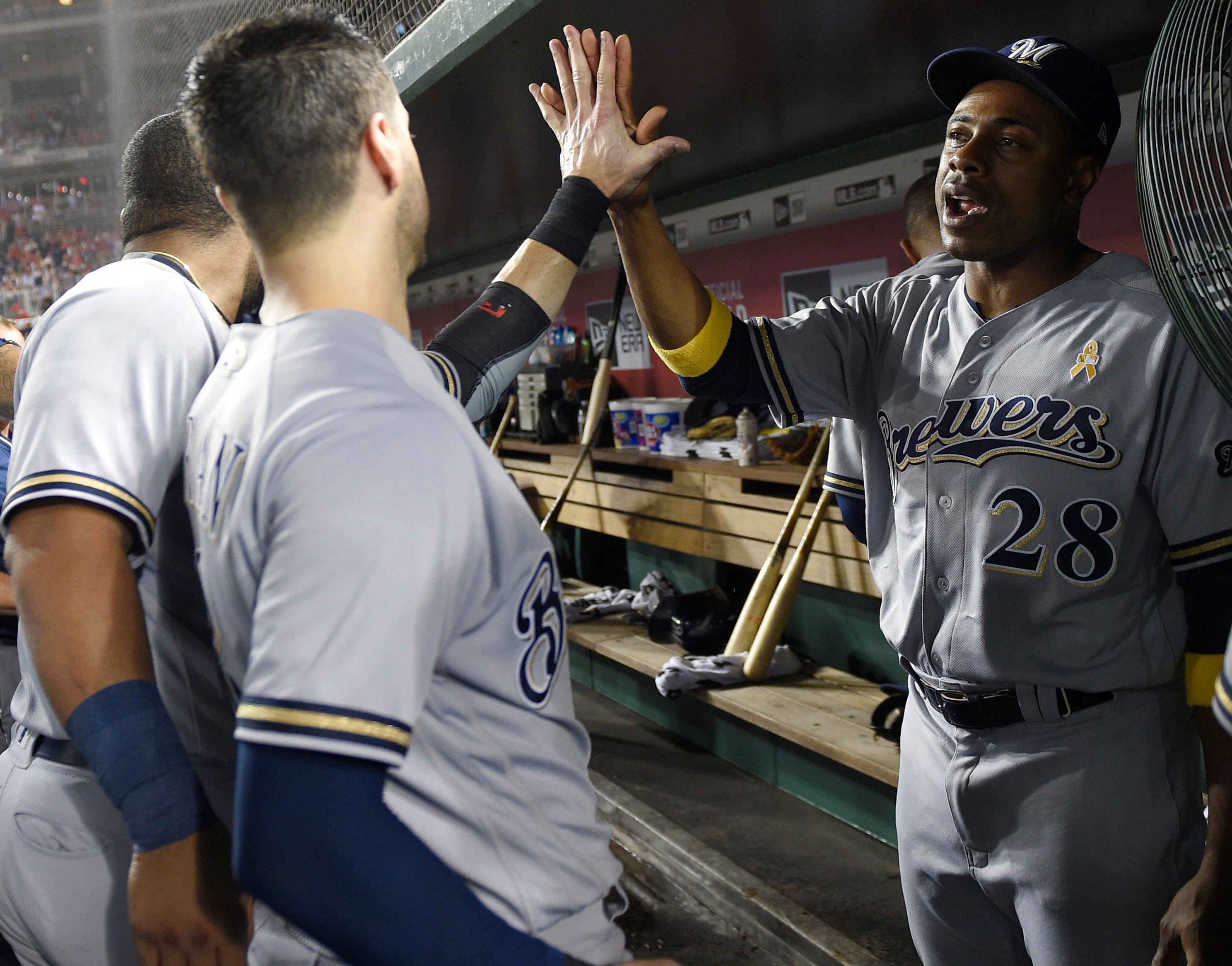 Curtis Granderson (right) gives a high-five to Brewers teammate Ryan Braun during a game against the Nationals.