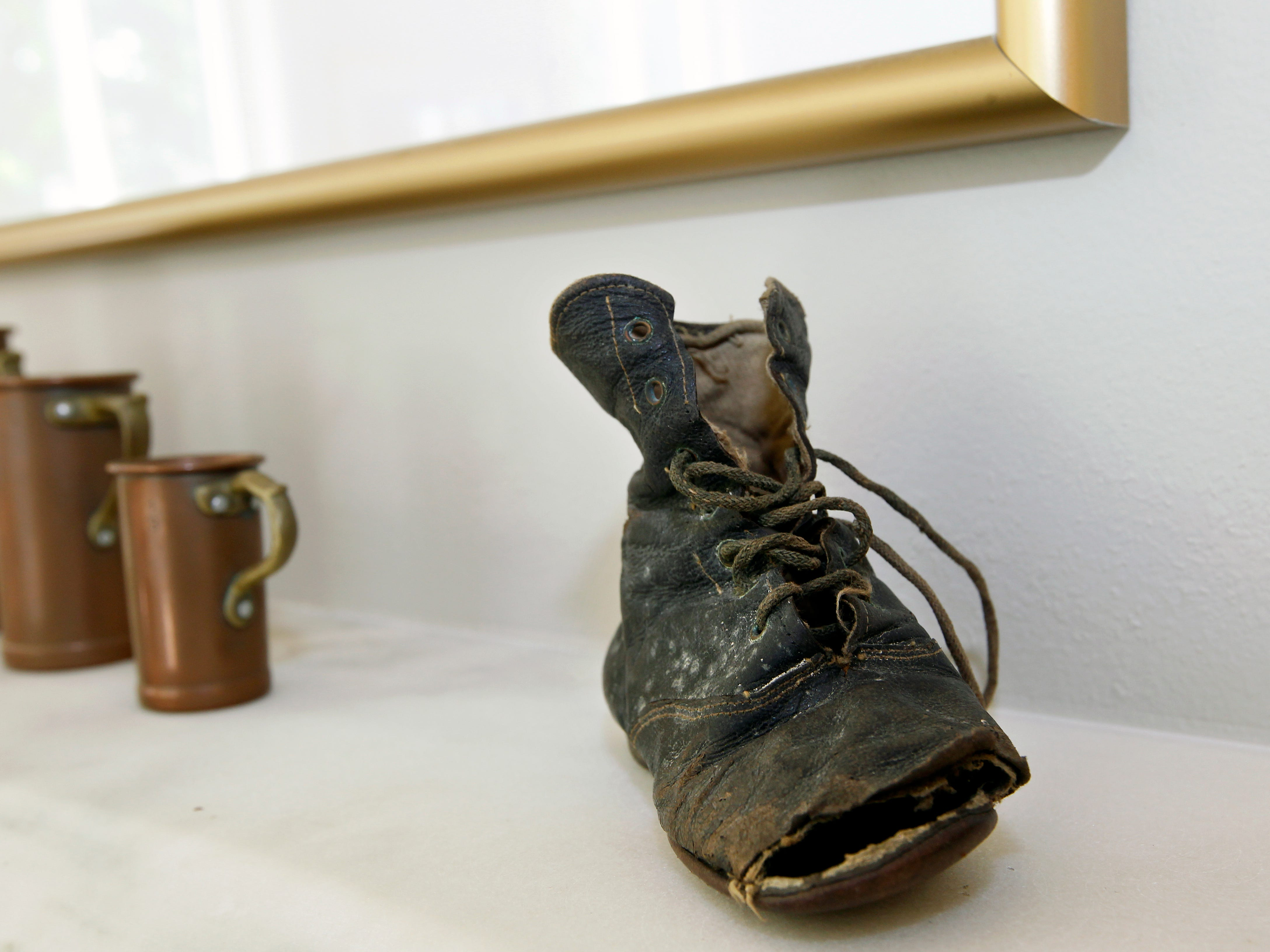 This child's shoe on displayed on the fireplace mantel was found in the wall by the previous owner.