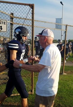Ronald Woolsey, 89, of Brookfield  gives fist bumps to Brookfield East football players during a Aug. 31 game.