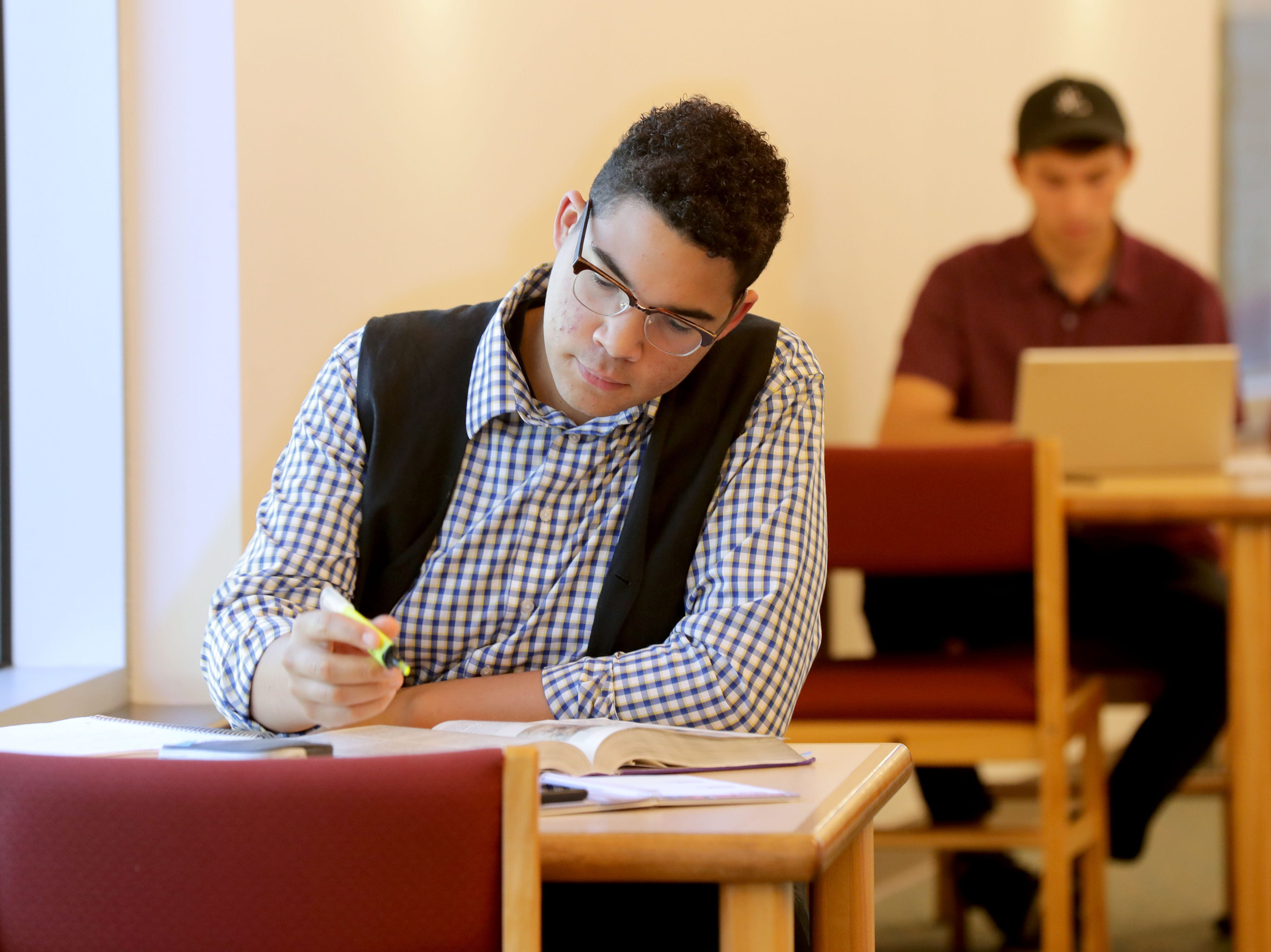 Steven Bullock, a senior at Sheboygan Lutheran High School taking a college class, studies at the University of Wisconsin-Green Bay, Sheboygan Campus library.