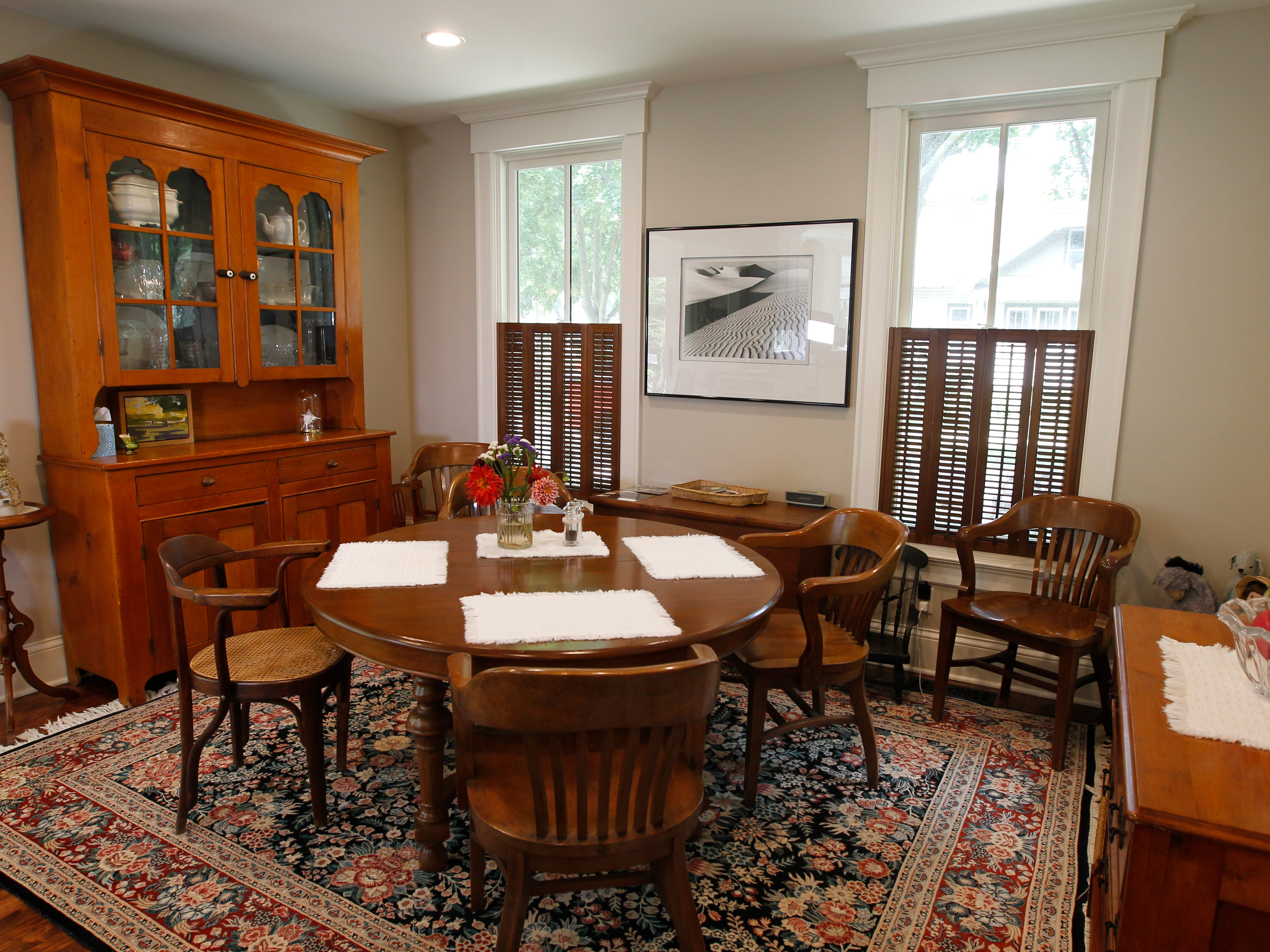 The dining area includes an antique pumpkin pine breakfront on the far left and a chest  of drawers from the Civil War era in the lower right.