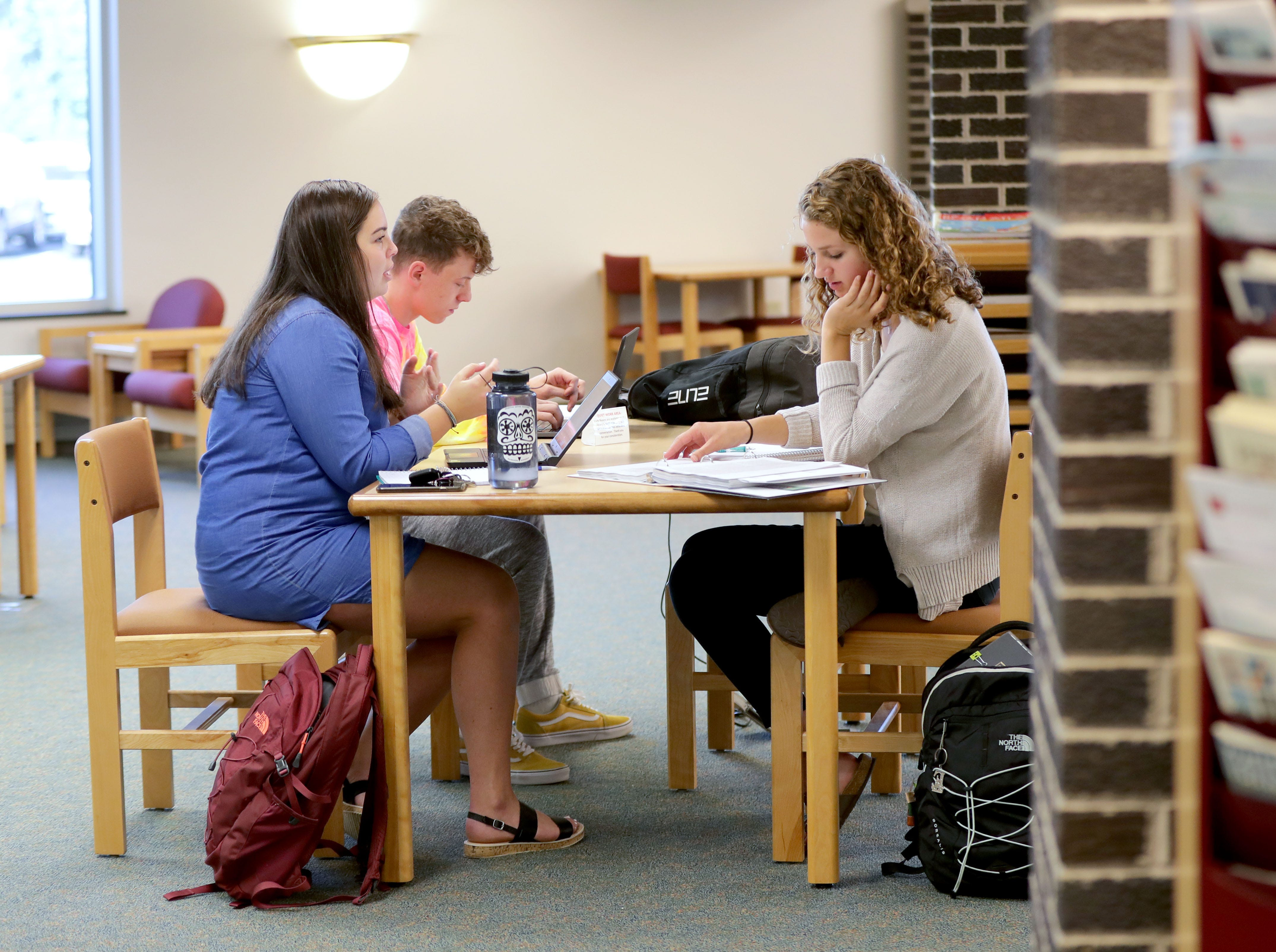 Madison Vogel (front left), a University of Wisconsin-Green Bay, Sheboygan Campus freshman from Kiel, Emma Egbert (right), a senior at Sheboygan Lutheran High School taking a college class, and Justin Landgraf, a University of Wisconsin-Green Bay, Sheboygan Campus junior from Sheboygan, work on a project for their introduction to psychology class.