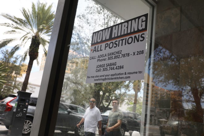 """A """"now hiring"""" sign is posted in a restaurant window Friday in Miami."""