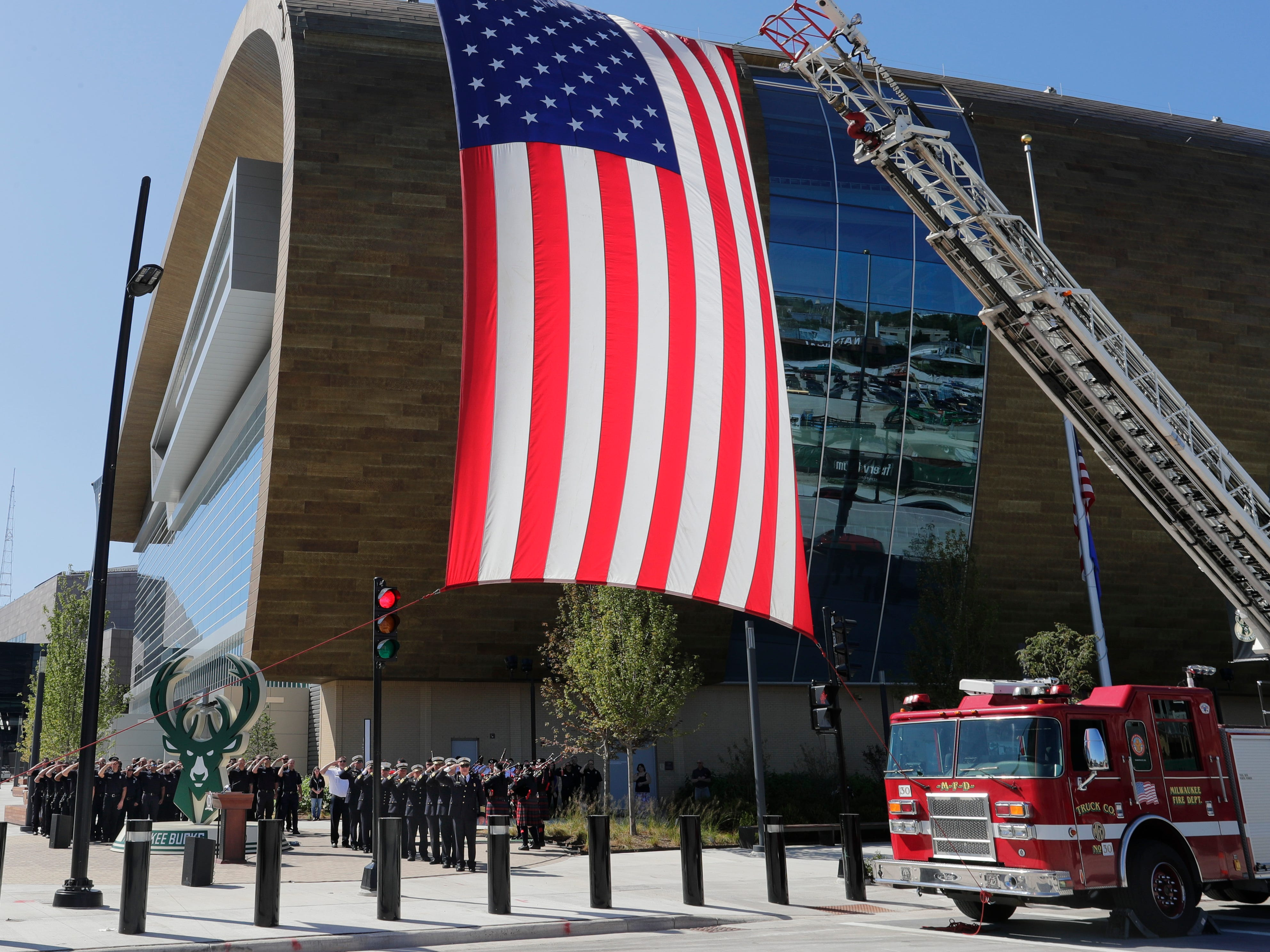 Two Milwaukee Fire Department ladder trucks display the American flag at the Fiserv Forum in an early morning commemoration for firefighters who lost their lives responding to the Sept. 11, 2001, attacks on the World Trade Center in New York.