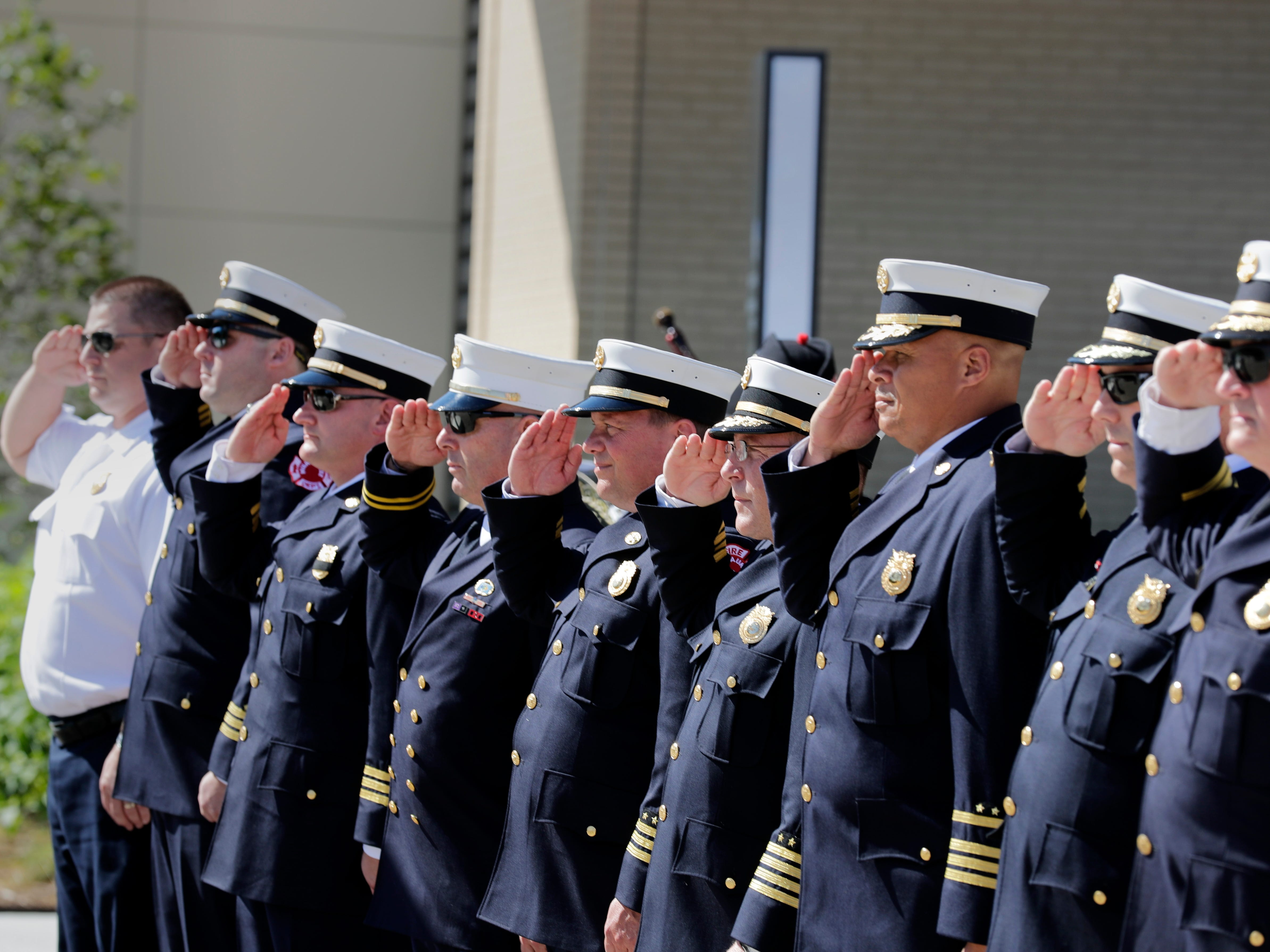Milwaukee Fire Department officials salute as they pay tribute to those who lost their lives in the 9-11 attacks.