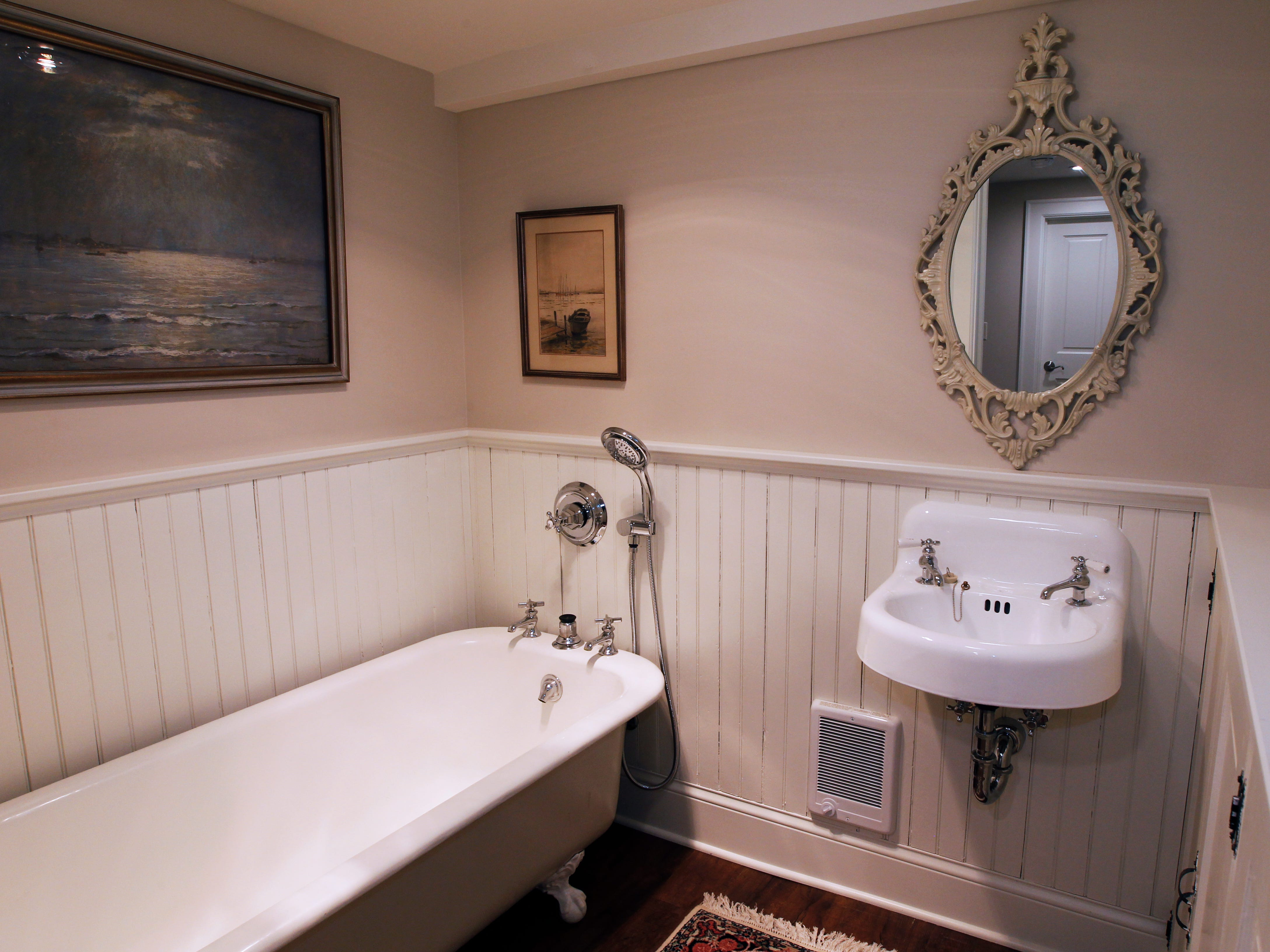 The downstairs bathroom features re-salvaged materials found throughout the house, including a clawfoot tub, sink and wainscoting.