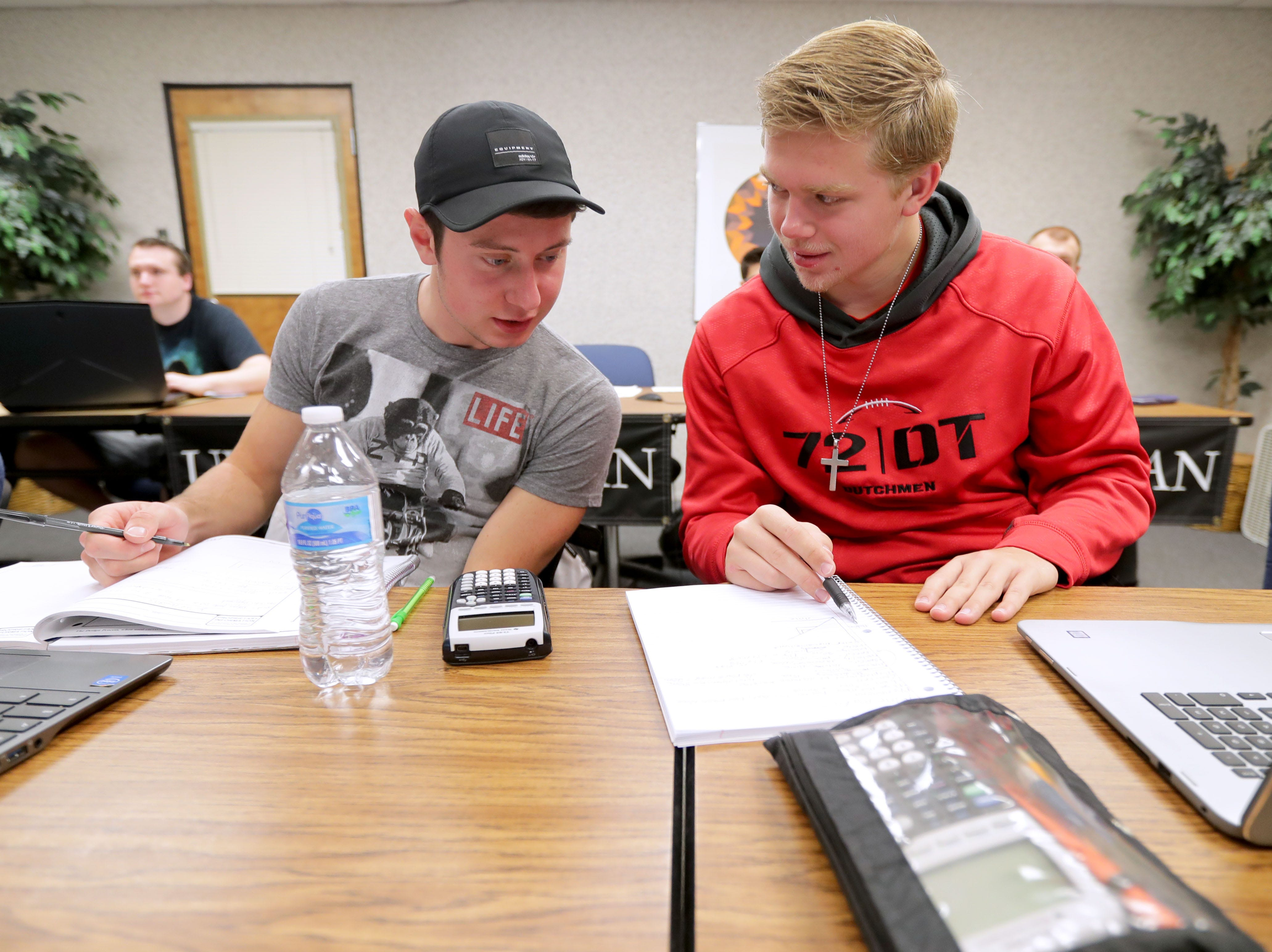 Jacob Eernisse (left), a University of Wisconsin-Green Bay, Sheboygan Campus freshman from Oostburg, and Mitchell Ver Velde, a sophomore from Oostburg, work together during a college physics class. The class was being taught remotely via a video conference by Thomas Hall from the University of Wisconsin-Whitewater at Rock County campus.
