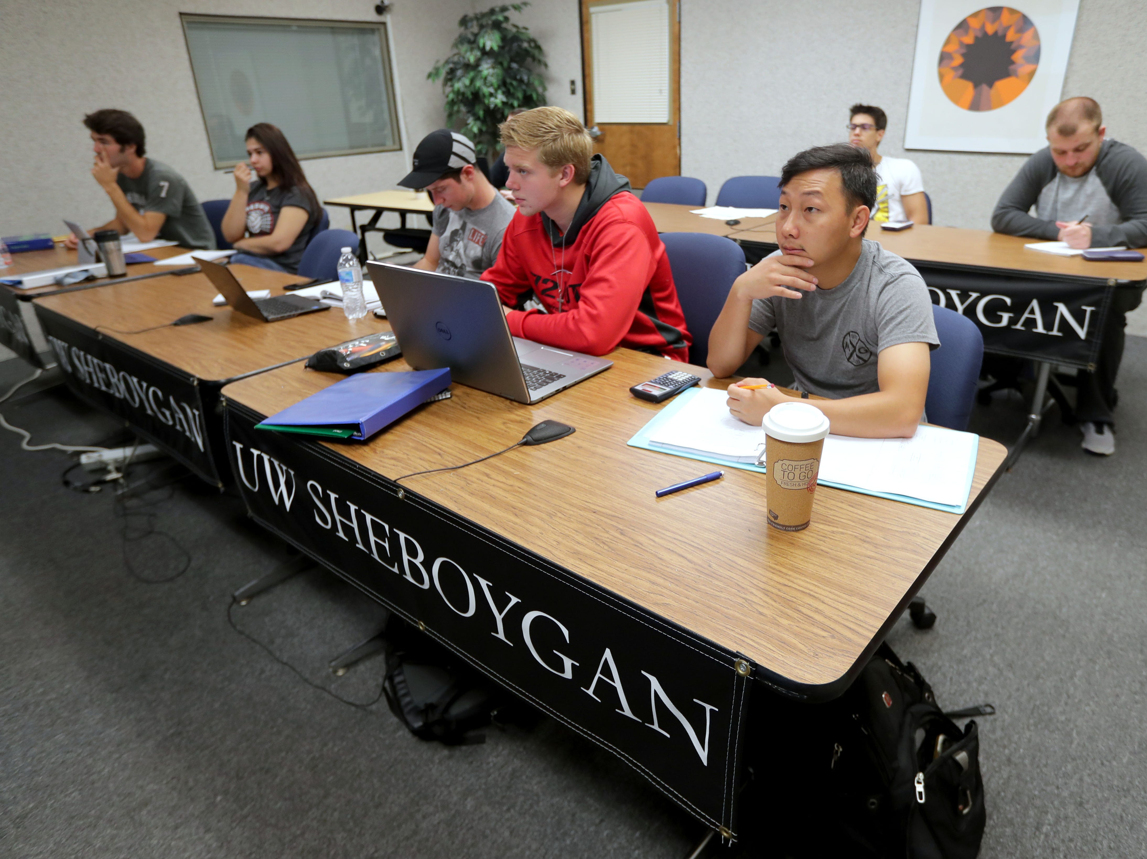 University of Wisconsin-Green Bay, Sheboygan Campus students Jacob Eernisse (front right table from left), a freshman from Oostburg; Mitchell Ver Velde, a sophomore from Oostburg; and Xiong Yang, a sophomore from Sheboygan, participate in a physics class  being taught by Thomas Hall remotely via a video conference from the University of Wisconsin-Whitewater at Rock County.