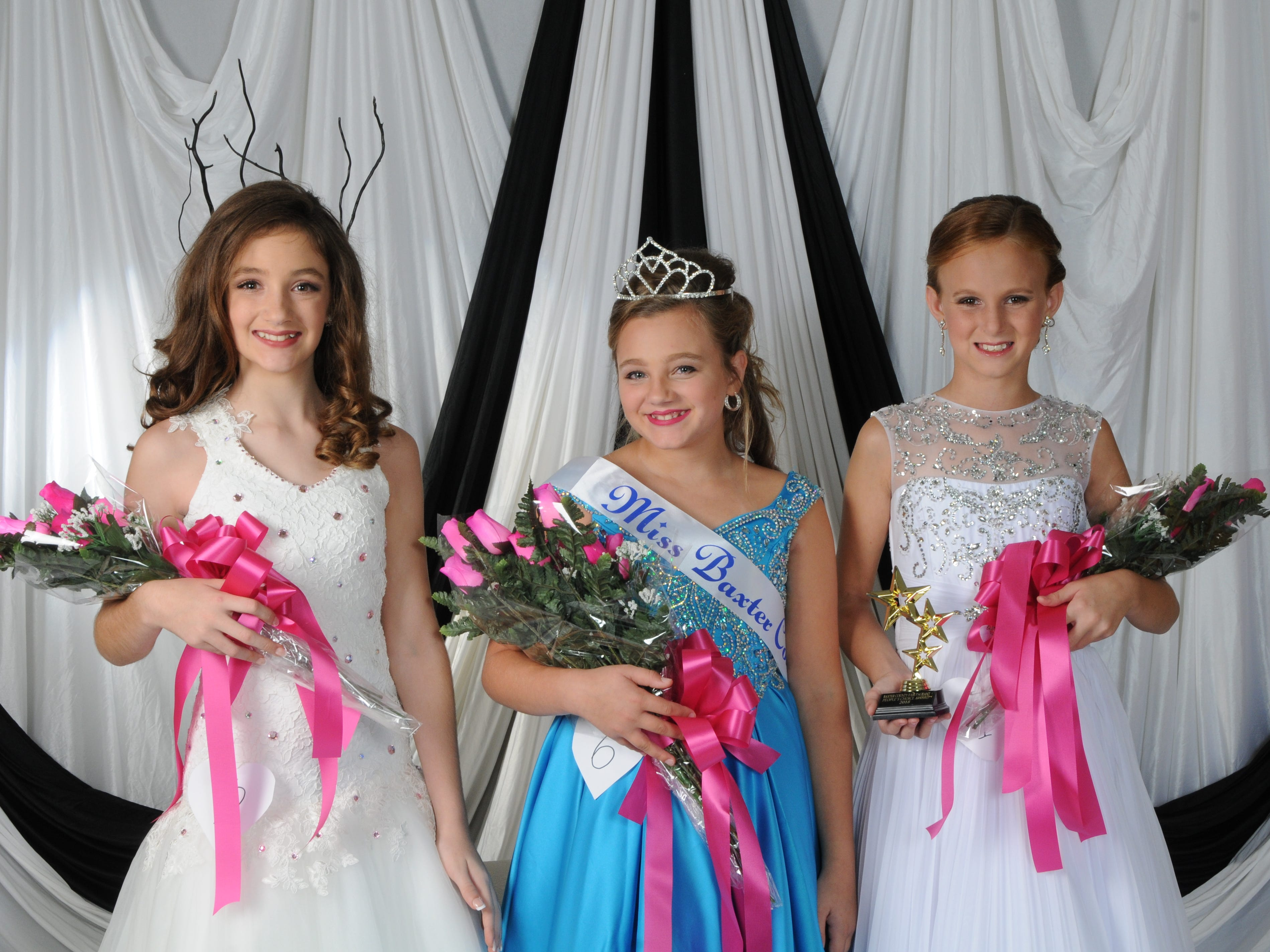 Marlee Shields (center), daughter of Sammie and Monica Shields of Norfork, was named Miss Baxter County at the annual Baxter County Fair Pageant on Saturday at Dunbar Auditorium. Audrian Litty (right), daughter of Ryan and Chelsea Kaye of Mountain Home and Bo Litty of Mountain Home, was named first alternate; and Alexia Loudermilk (left), daughter of Paul and Kelli Loudermilk of Gassville, was named second alternate. Litty was also the People's Choice winner.