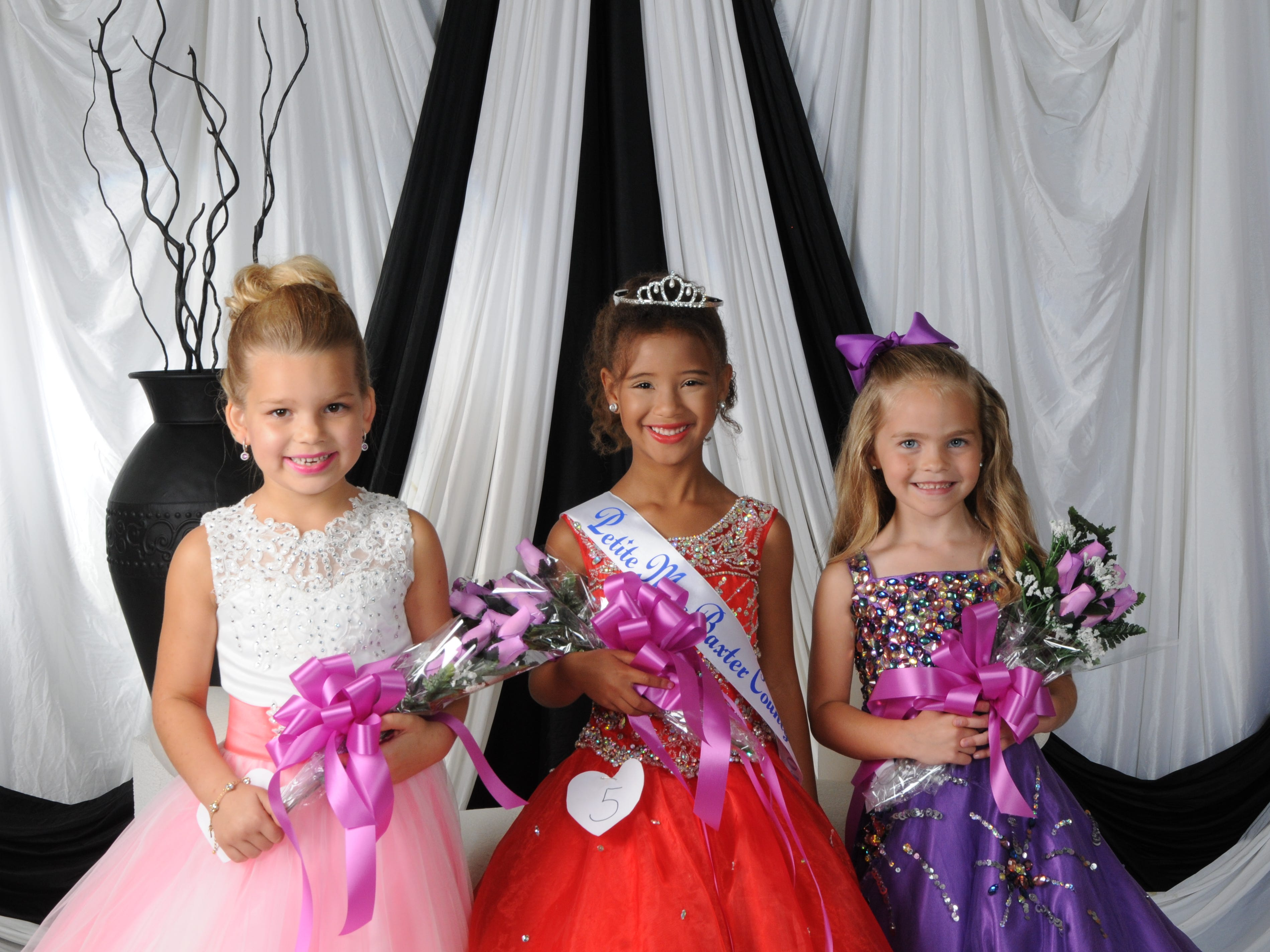 Samira Gassama (center), daughter of Travis and Stephonie Ifland of Mountain Home, was named Petite Miss Baxter County at the annual Baxter County Fair Pageant on Saturday at Dunbar Auditorium. Rylee Jones (right), daughter of Wesley and Angelica Jones of Mountain Home, was named first alternate; Heleyna Koenen (left), daughter of Jacob and Constance Koenen of Mountain Home, was named second alternate; and Zoey Kaye (not pictured), daughter of Stephanie and Luke Spence of Mountain Home and Ryan and Chelsea Kaye of Mountain Home, was named the People's Choice winner.