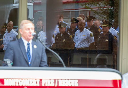 Montgomery police and firefighters are reflected in the windows of the fire station as Director of Public Safety Ronald Sams gives opening remarks.