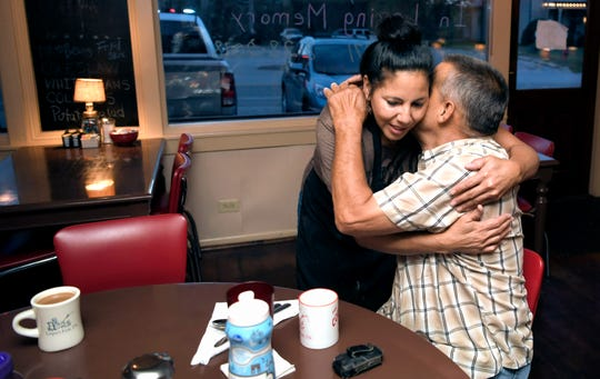 Country Boy restaurant owner Diana Torres hugs longtime customer Jud Whidby as the restaurant opens for breakfast on Sept. 11, 2018.