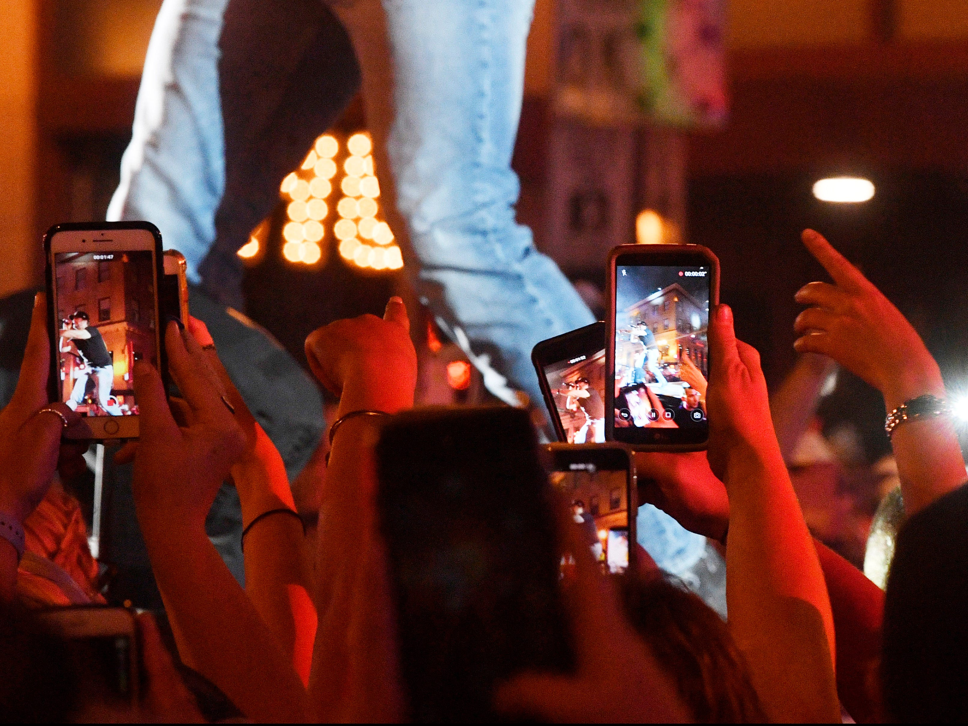 Fans photograph Luke Bryan up close as he plays a free concert for fans in front of his new bar Luke's 32 Bridge at 3rd and Broadway Monday Sept. 10, 2018, in Nashville, Tenn.
