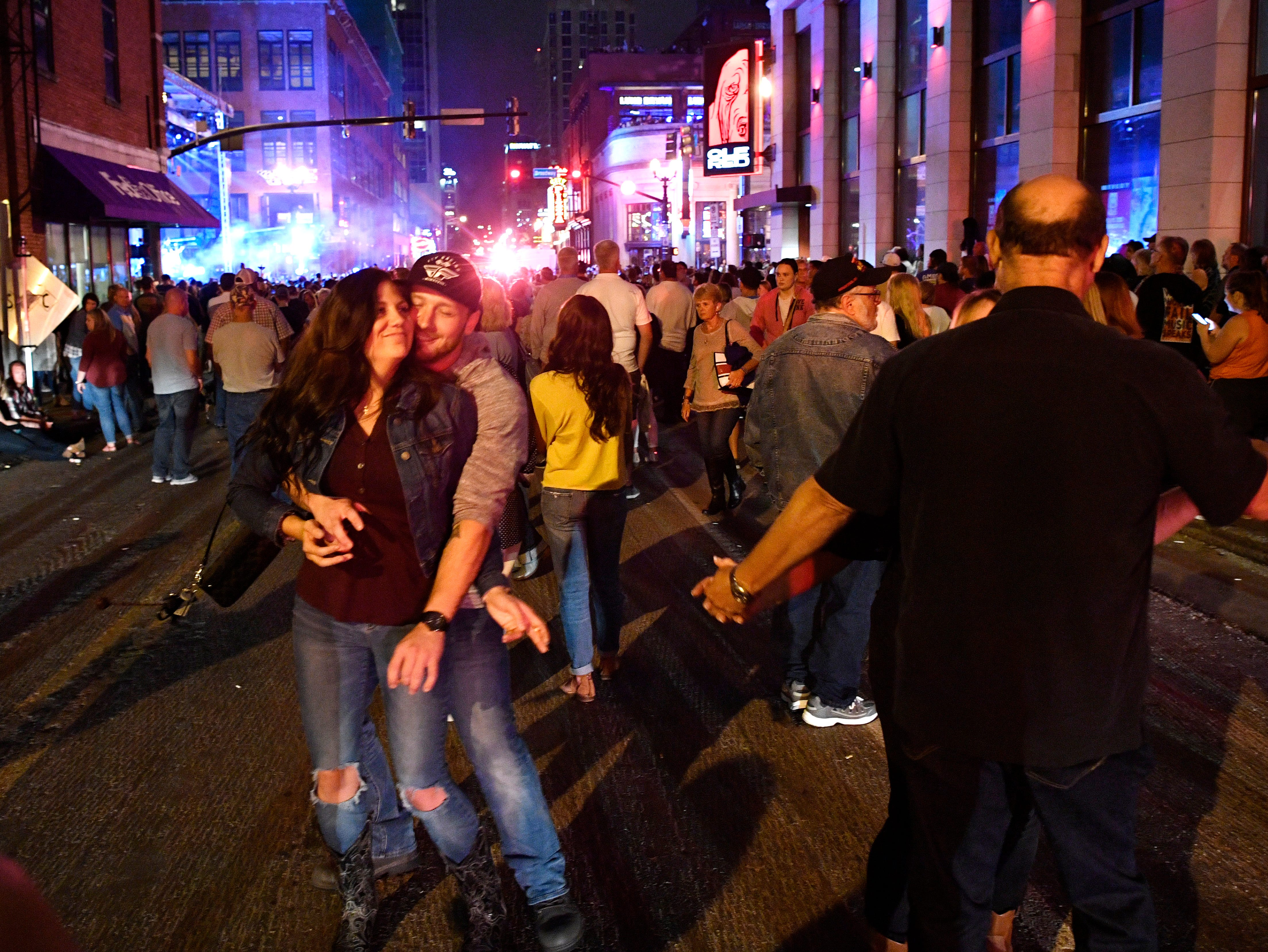 Fans dance to the music as Luke Bryan performs a concert for fans in front of his new bar Luke's 32 Bridge at 3rd and Broadway Monday Sept. 10, 2018, in Nashville, Tenn.