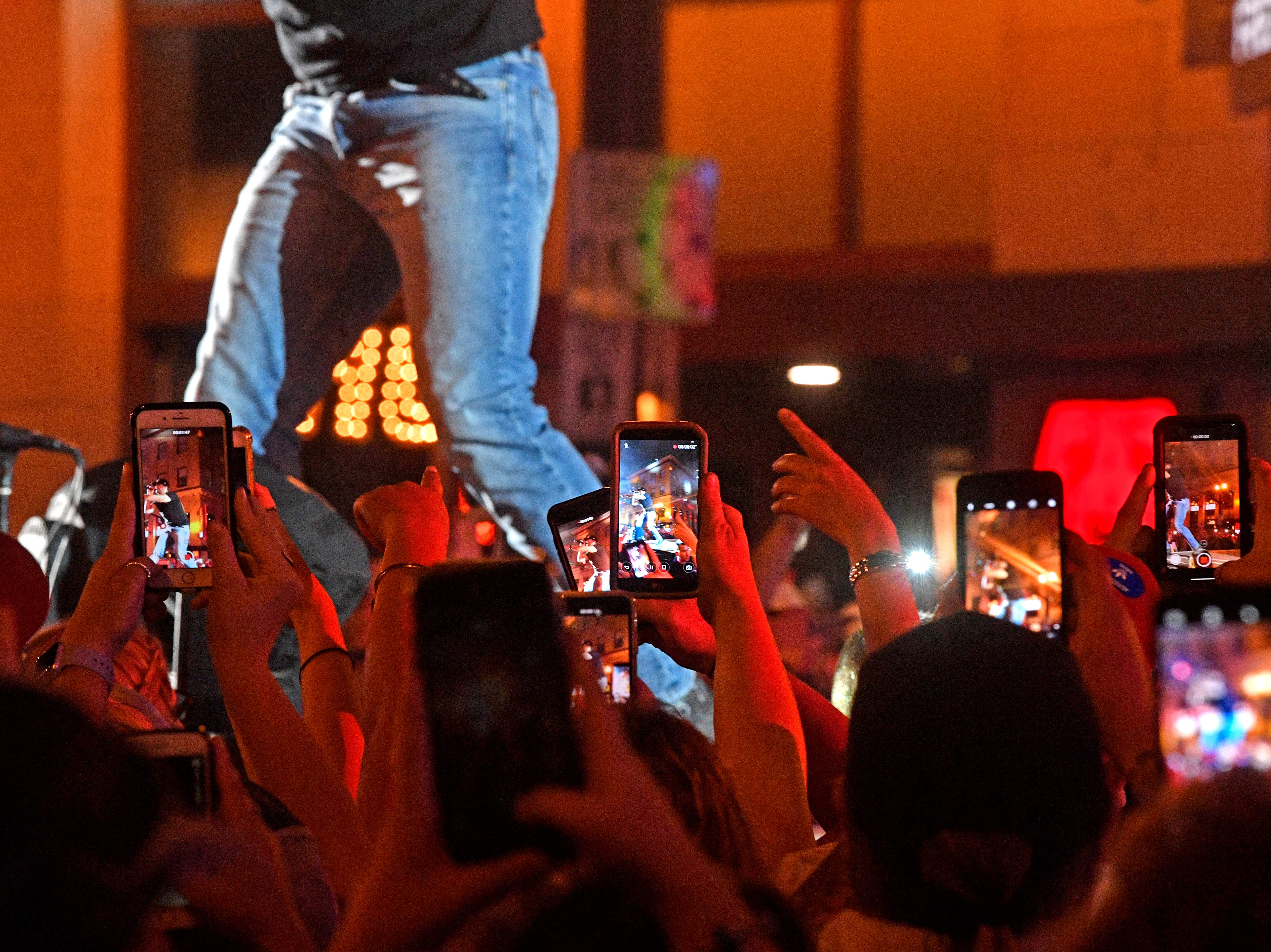 Fans get out their cell phones to get a close up photo as Luke Bryan performs a concert for fans in front of his new bar Luke's 32 Bridge at 3rd and Broadway Monday Sept. 10, 2018, in Nashville, Tenn.