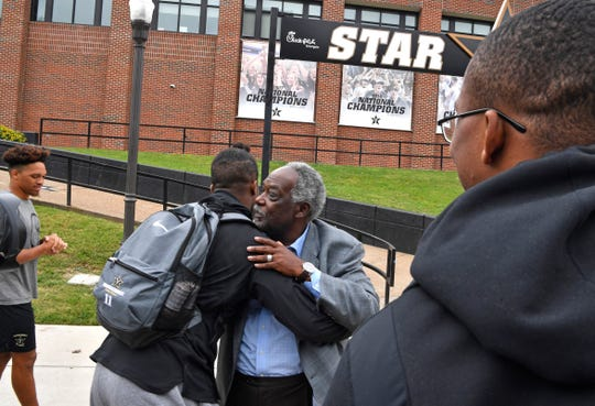 Vanderbilt athletics director David Williams is hugged by several football players as he walks to a press conference where he confirmed he will resign as athletics director and vice chancellor