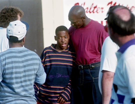Former NBA star and Birmingham Barons player Michael Jordan, center right, hugs the dazed John Trotwood Moore Middle School student Michael Phillips as he checks on his condition at Greer Stadium April 24, 1994. Phillips, who a classmate and friend of Terrance Murray, who was killed at school April 21, was knocked to the ground by a security officer after he jumped the fence and ran on the field to ask Jordan to attend Murray's funeral.