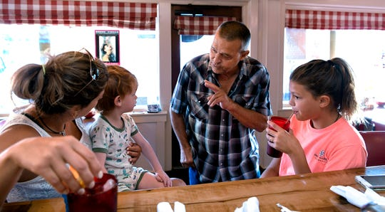 Country Boy restaurant longtime customer Jud Whidby greets longtime customer Cristin Minge and her children, Barron and Carolina, during breakfast at the Leipers Fork restaurant on August 29, 2018.