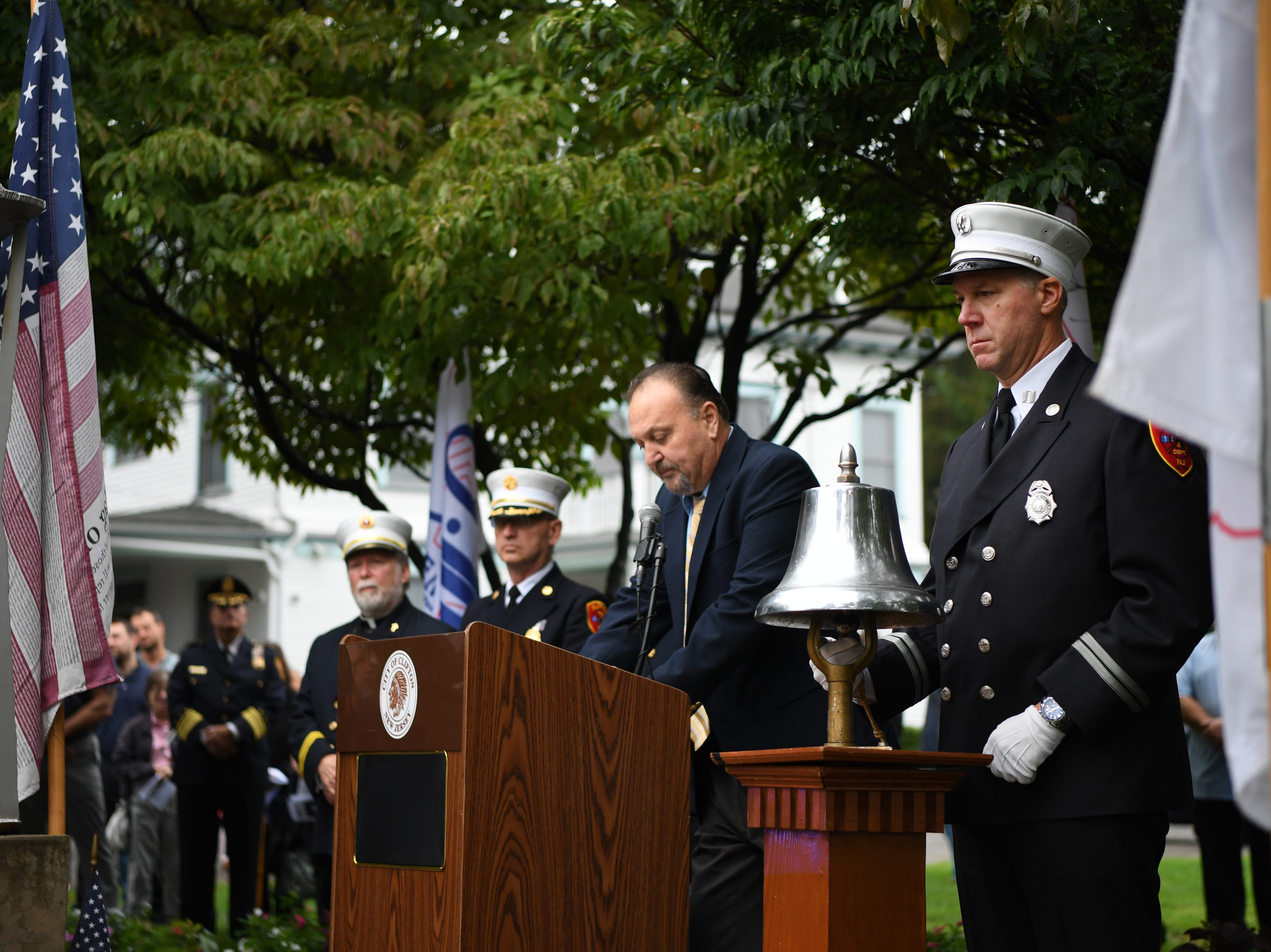 Clifton Fire Captain Daniel Collins rings a bell as the names of Clifton residents lost on 9/11 are read during a 9/11 memorial service at Clifton City Hall on Tuesday, September 11, 2018.