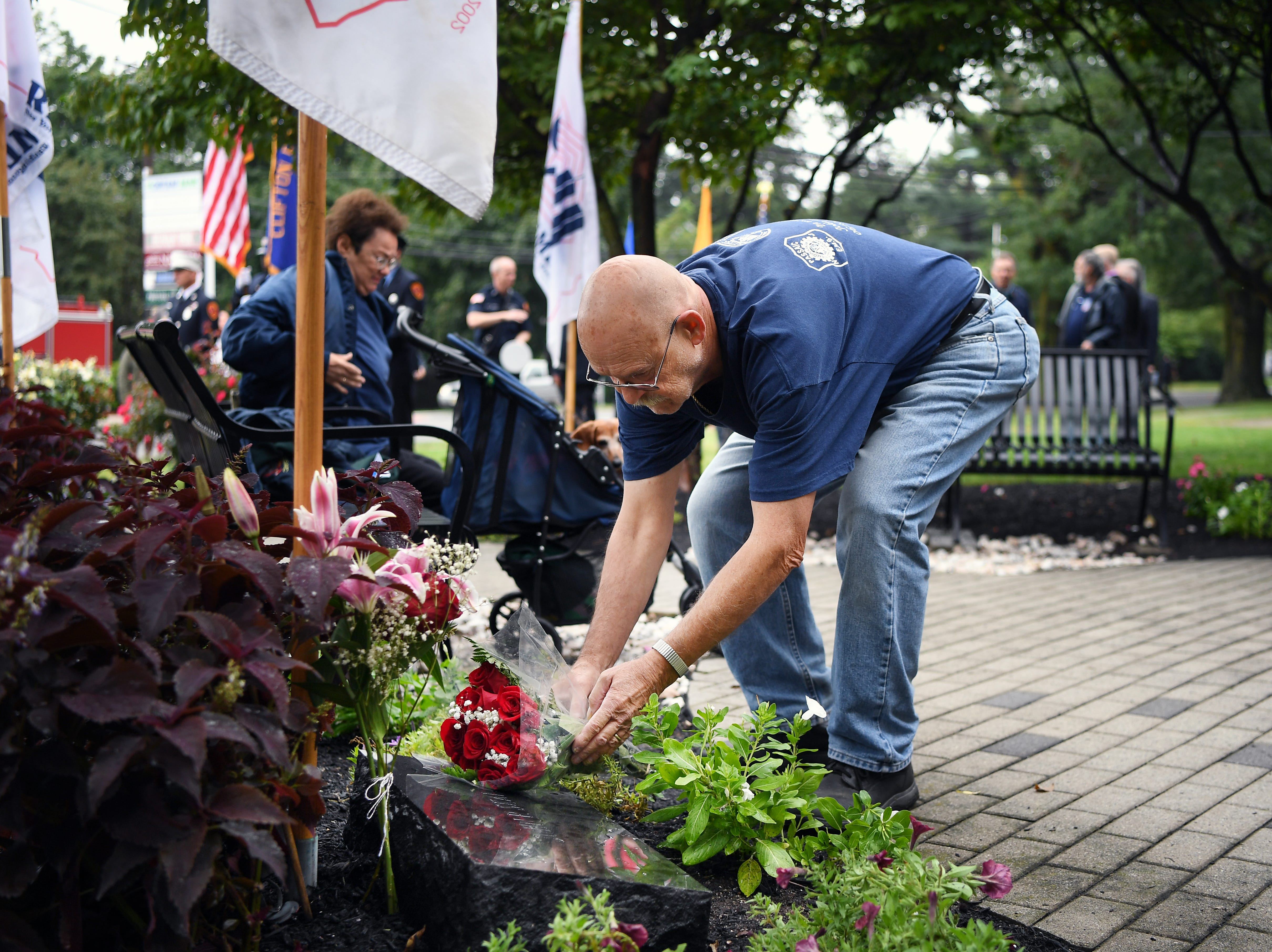 Robert Yuhas places flowers on a memorial for Port Authority Police Officer John Skala Jr. during a 9/11 memorial service at Clifton City Hall on Tuesday, September 11, 2018. John Skala Jr. was a Clifton resident who also worked as a part-time Emergency Medical Technician. He was killed on 9/11.