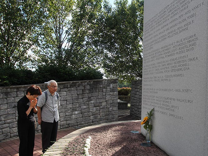 Mari Sugiyama (71) and her husband Kazusada (75) from Tokyo, Japan whose son Yoichi Sugiyama (at age 34 died in the World Trade Center) pray in front of the Bergen County 9/11 monument following the Bergen County 9/11 Remembrance Ceremony at the 9/11 Memorial in Overpeck Park in Leonia on 09/09/12. They come every year to honor their son's memory.