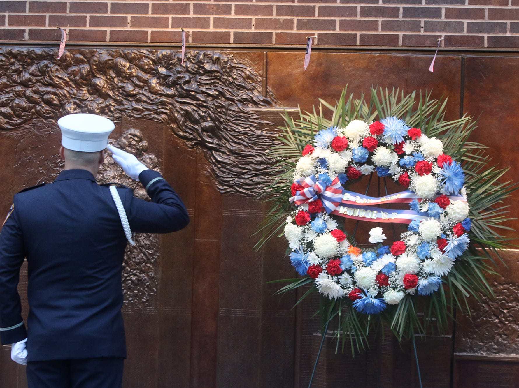 A member of the honor guard salutes the wreath hung at the memorial outside the building that houses Fire Co. 10, who lost members in the attacks of September 11, 2001 in lower Manhattan. This is prior to ceremonies at the National September 11 Memorial observing the 17th anniversary of the attacks that killed people in Manhattan, the Pentagon, Flight 93 and honoring those who died in the 1993 World Trade Center bombing.