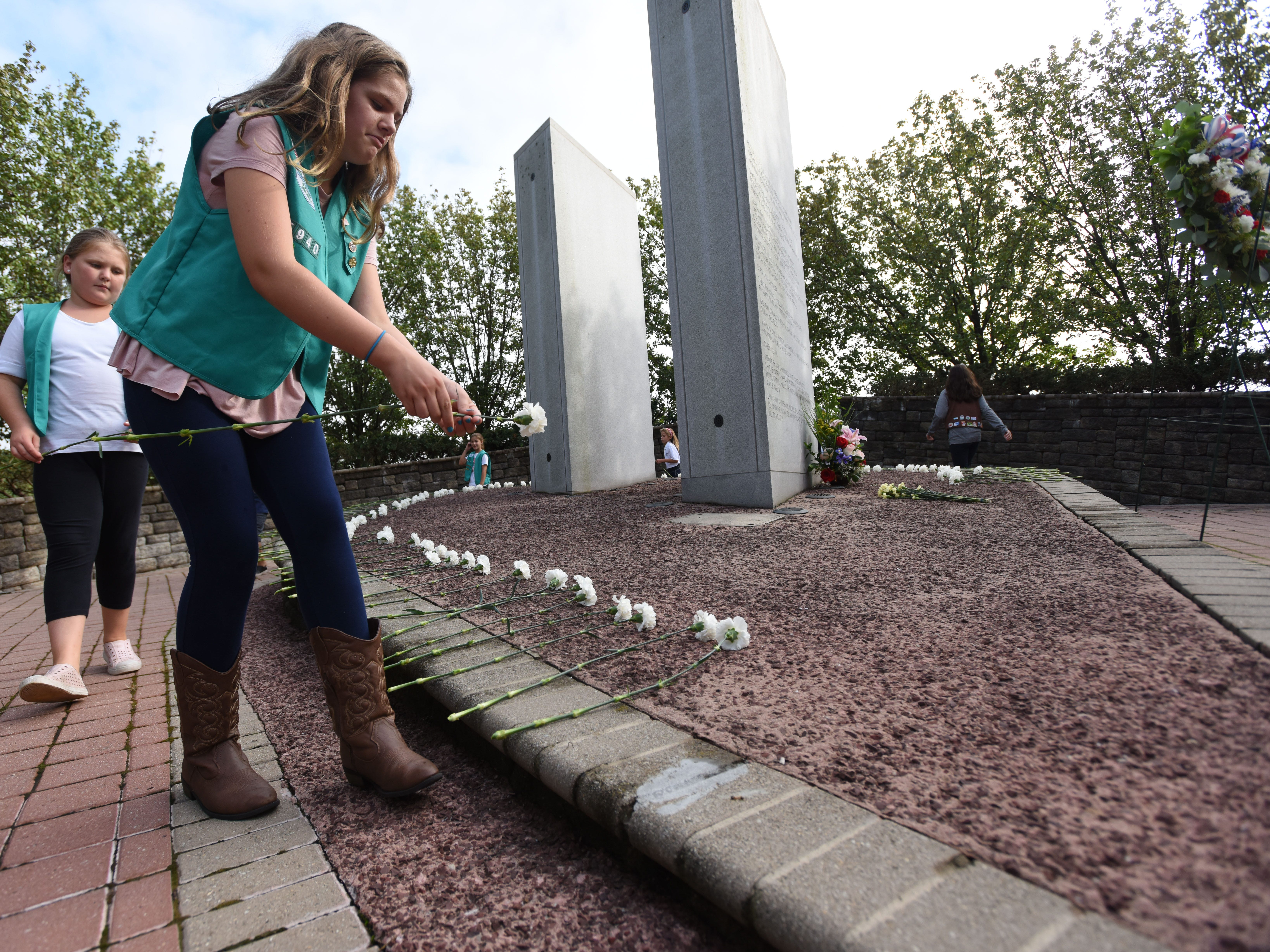 Members of Paramus and Ridgefield Park Girl Scouts lay flowers during the Bergen County 9/11 memorial ceremony in Overpeck Park