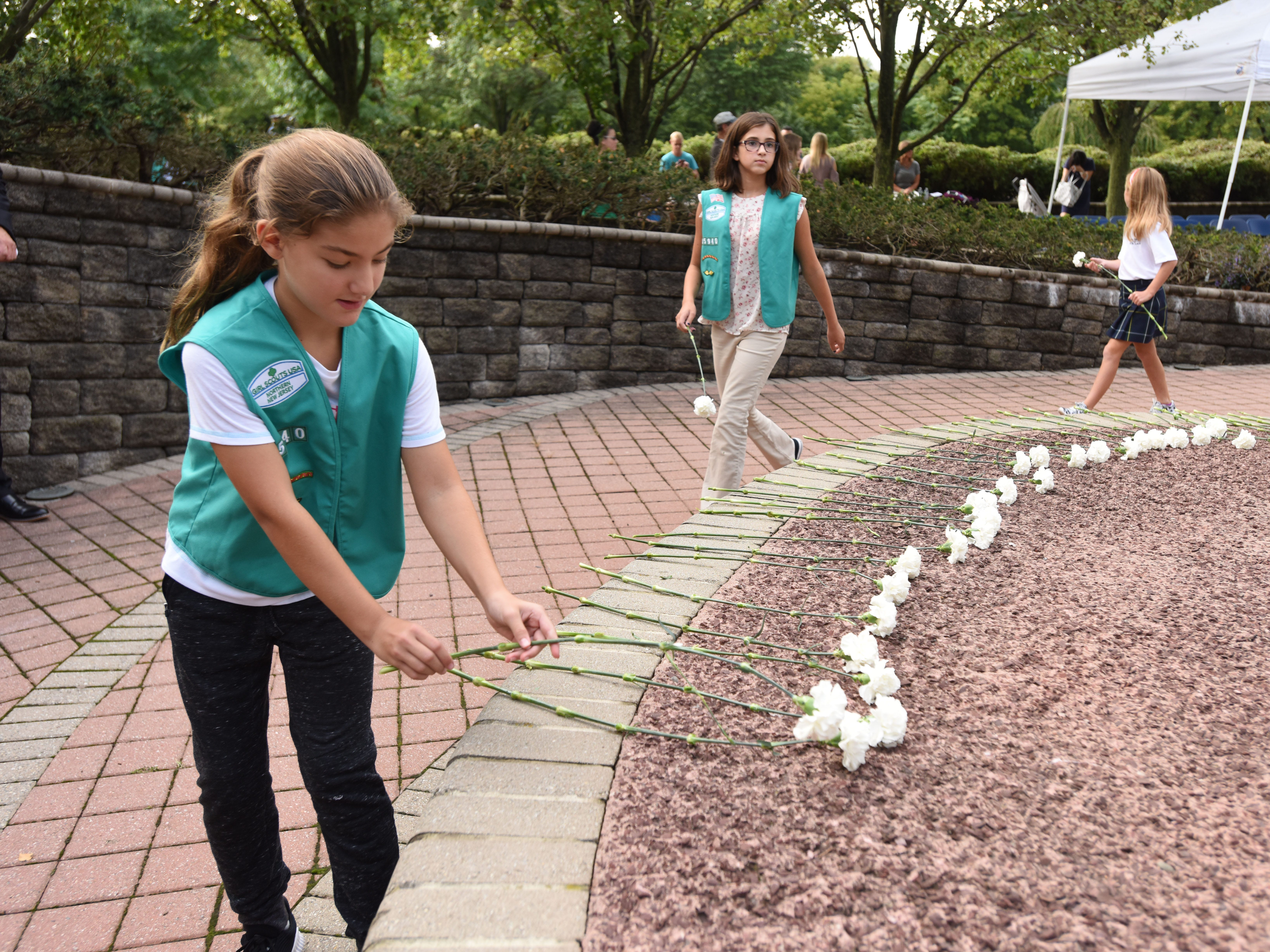 Members of Paramus and Ridgefield Park Girl Scouts lay flowers during the Bergen County 9/11 memorial ceremony in Overpeck Park.