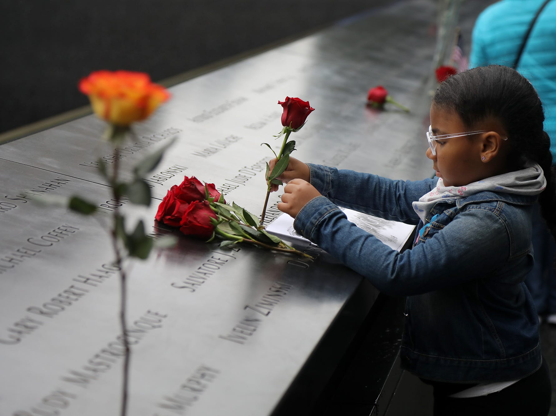 Emma Cordero 8 of the Bronx puts a flower in the name of her uncle Alejandro Cordero during ceremonies at the National September 11 Memorial observing the 17th anniversary of the attacks that killed people in Manhattan, the Pentagon, Flight 93 and honoring those who died in the 1993 World Trade Center bombing.
