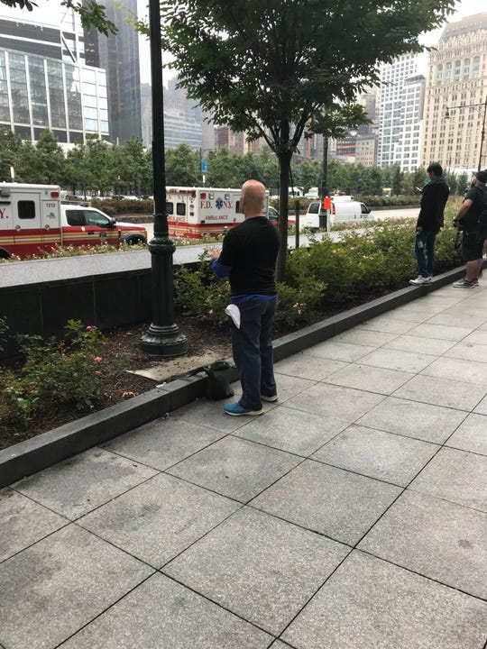 John Velez, 54, formerly of Union City, observes a moment of silence at 9/11 commemoration.  Velez, a furniture mover, took the day off to come to lower Manhattan.  He is standing on West Street, across from the memorial which was open only to relatives of victims and first responders.