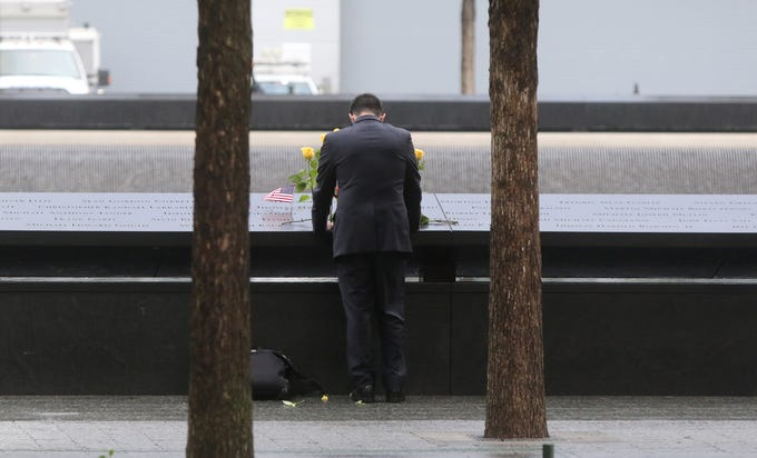 A man looks at names etched into granite, parts of the memorial pool for the North Tower prior to the ceremonies at the National September 11 Memorial observing the 17th anniversary of the attacks that killed people in Manhattan, the Pentagon, Flight 93 and honoring those who died in the 1993 World Trade Center bombing.