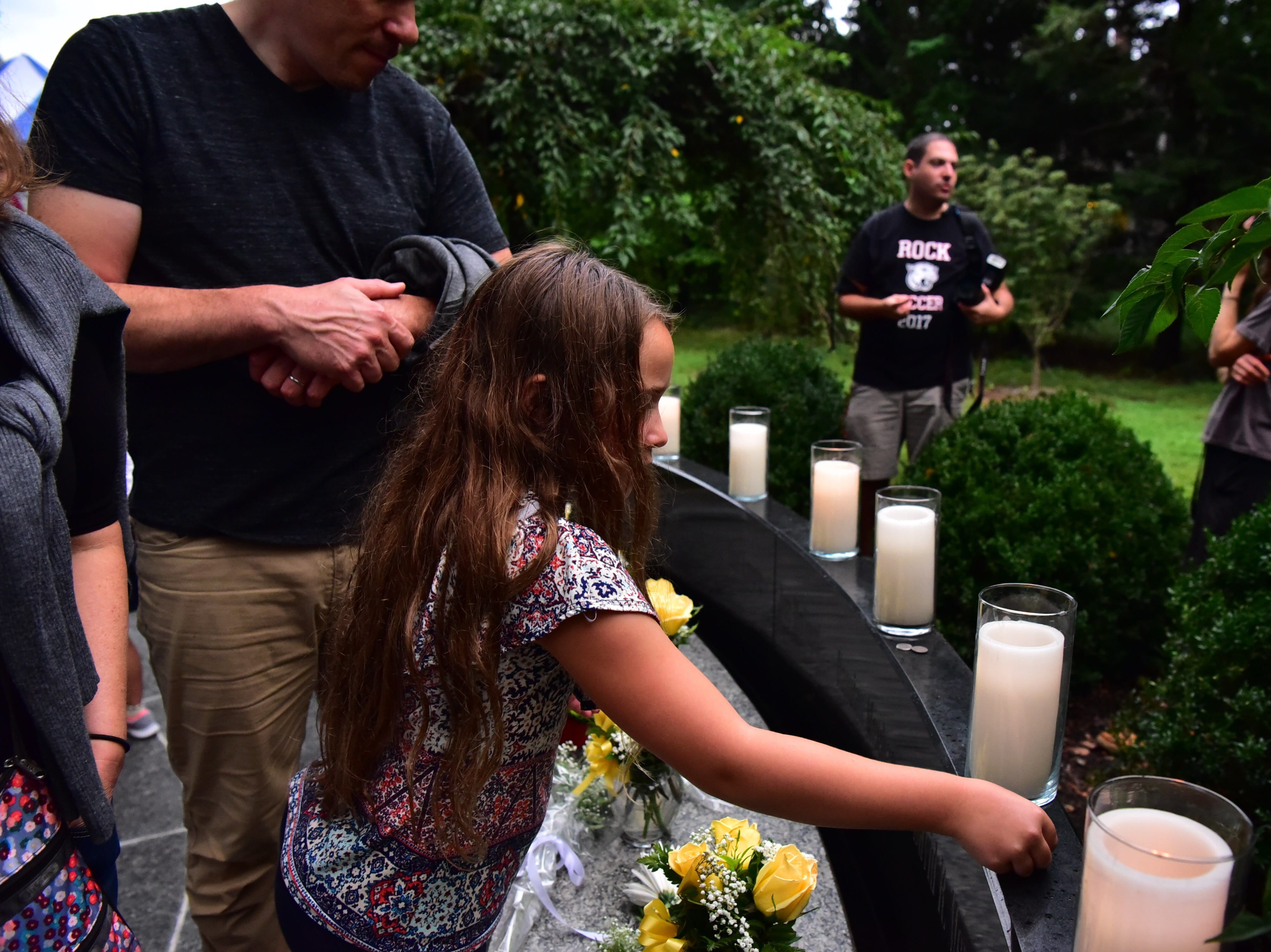 Charlotte Mayer-Fuchs, 8, pays respect to her grand father who died on 9-11, in Glen Rock, NJ.