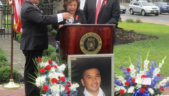 Maria Arevallo speaks at ceremony honoring her son, Keneth Lira, a 9/11 victim. She is flanked by another son, Michael Lira, left, and Paterson Mayor Andre Sayegh, who had been a grade school classmate of the deceased. A photo of the victim is in front of the podium.