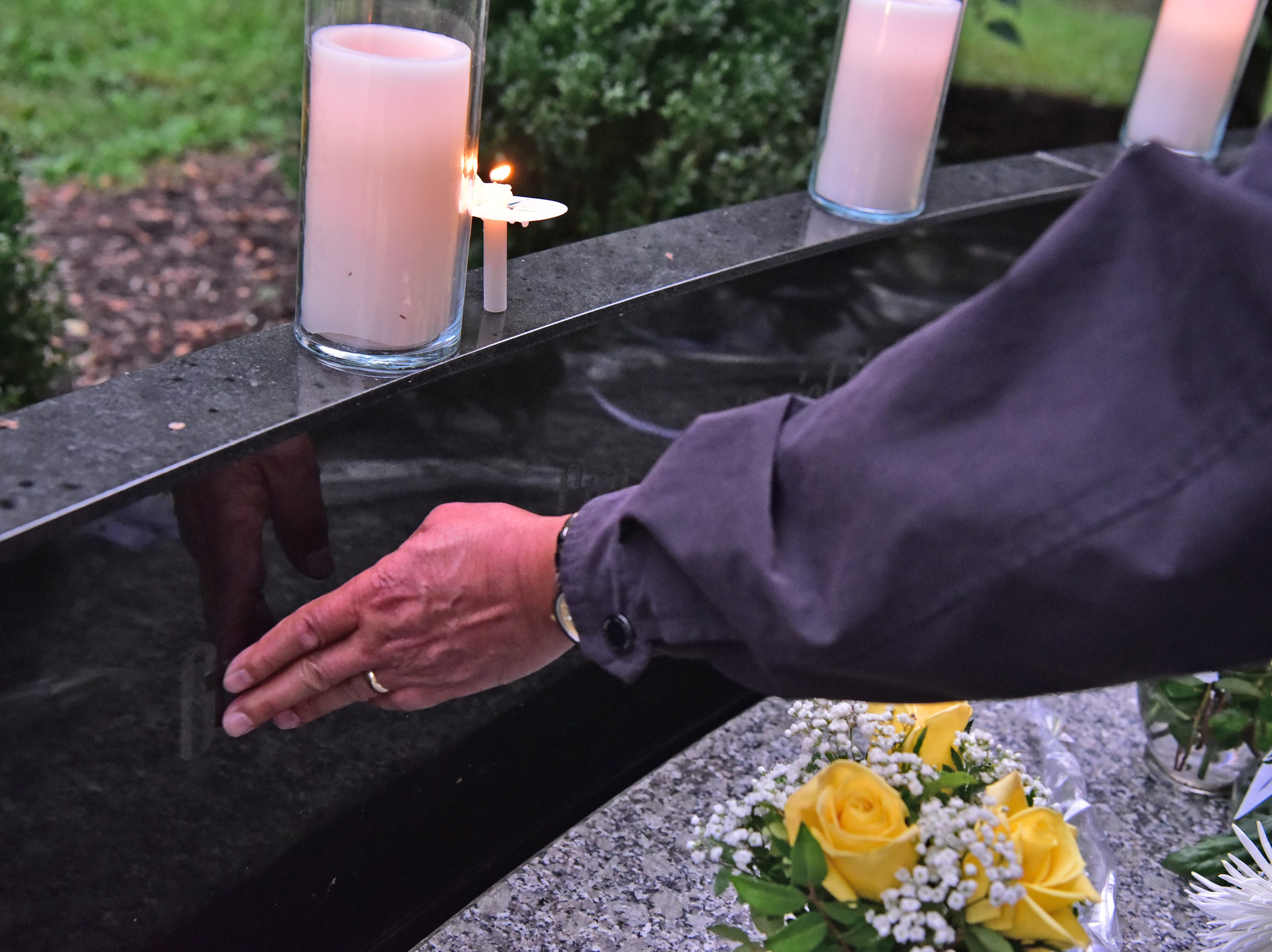 A person wipes the name of a 9-11 victim etched at the memorial in Glen Rock, NJ.
