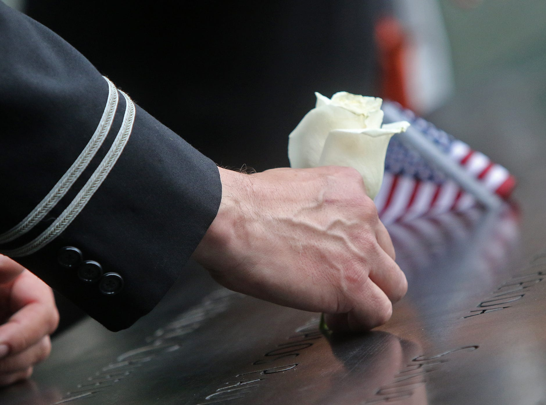 Flight attendant from Long Island, Gregory Davidowitch puts a flower in the name of his friend, Prokopios Paul Zios   during ceremonies at the National September 11 Memorial observing the 17th anniversary of the attacks that killed people in Manhattan, the Pentagon, Flight 93 and honoring those who died in the 1993 World Trade Center bombing.